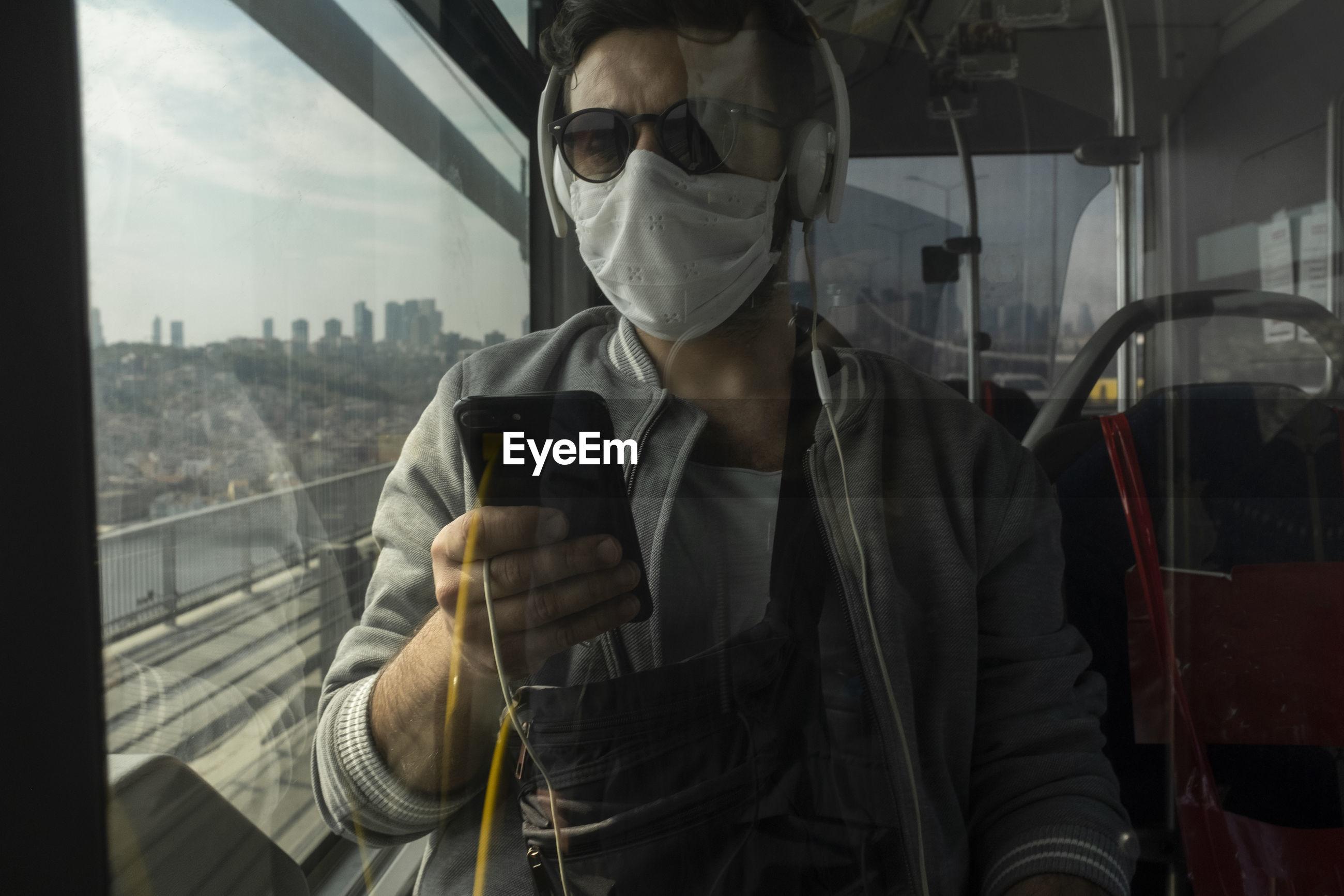 Man using mobile phone in train seen through window