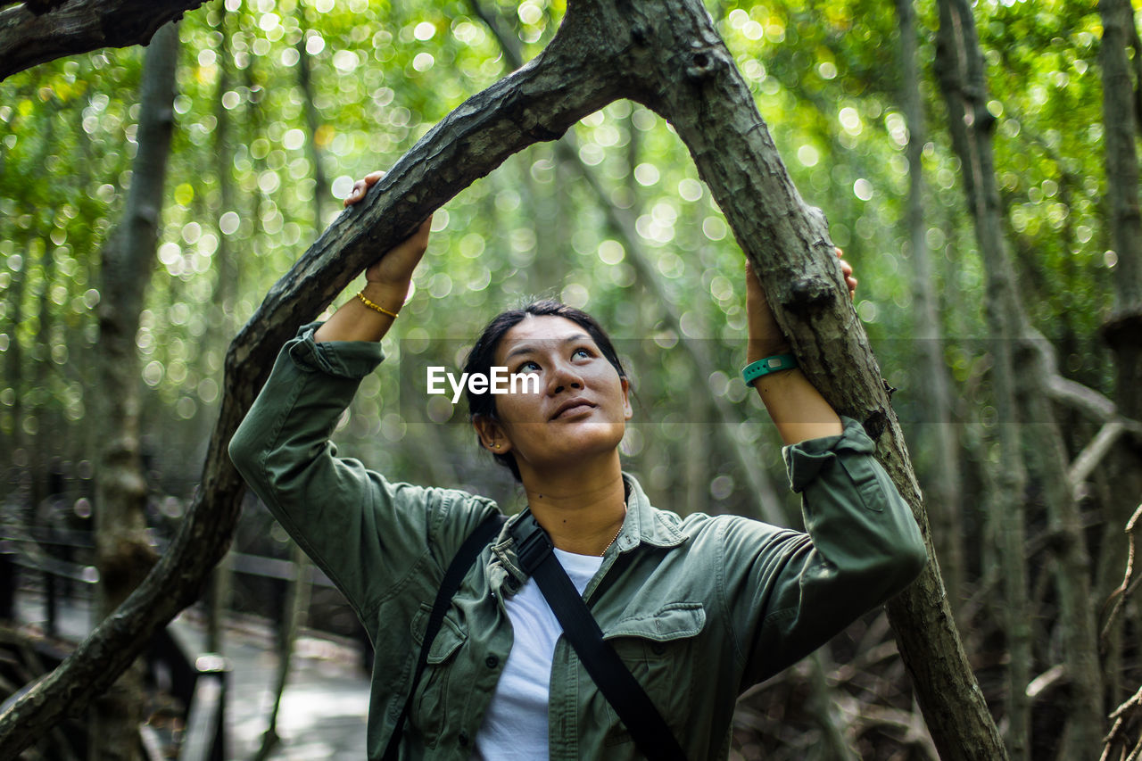 Smiling woman looking up while standing amidst trees in forest
