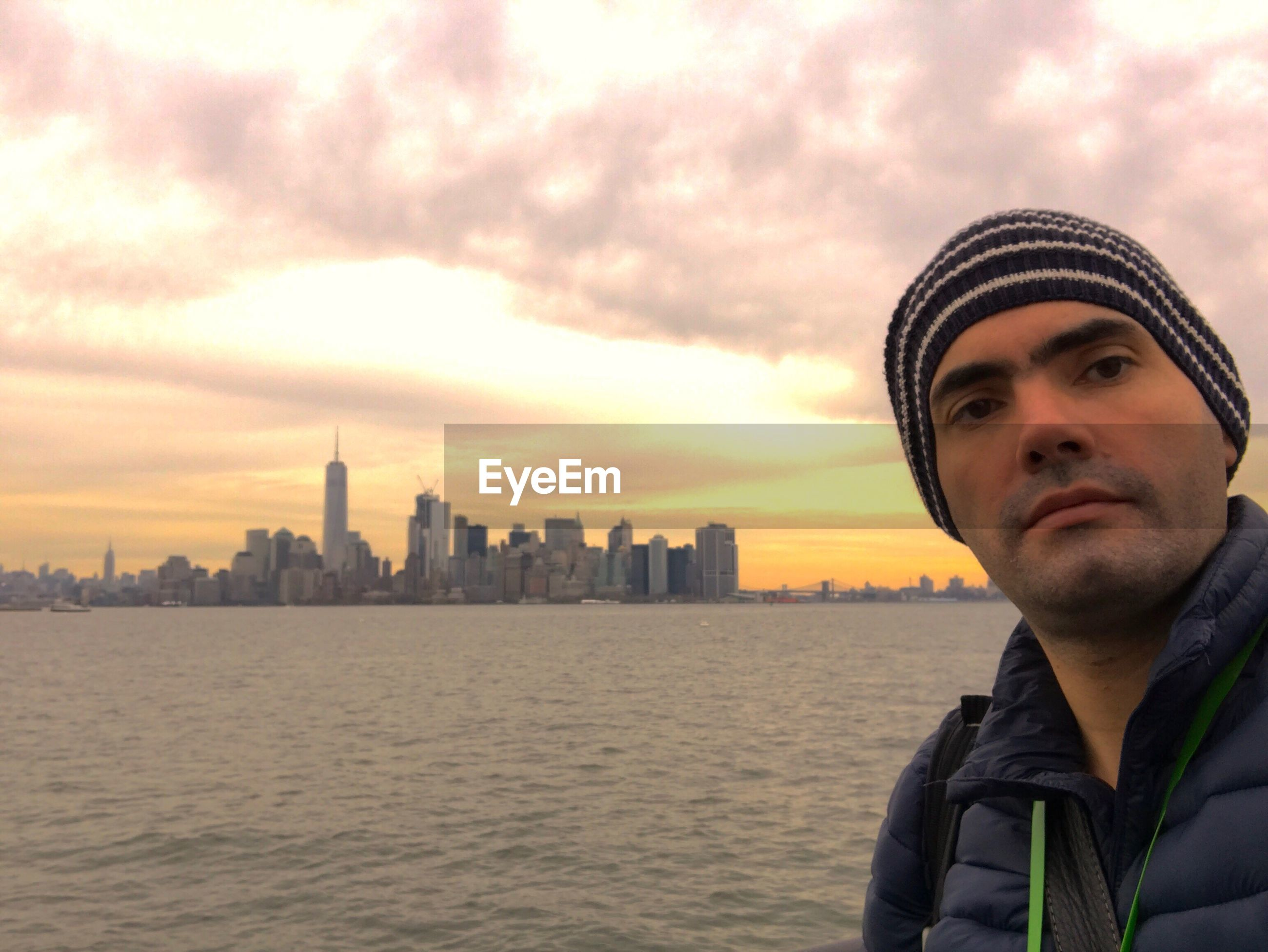 Man by hudson river against cloudy sky during sunset in city