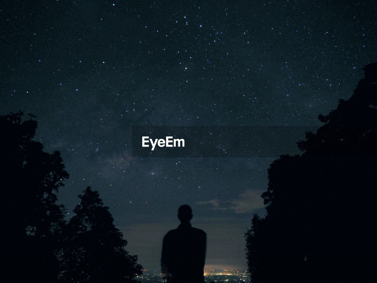 Rear View Of Silhouette Person Standing Against Star Field At Night