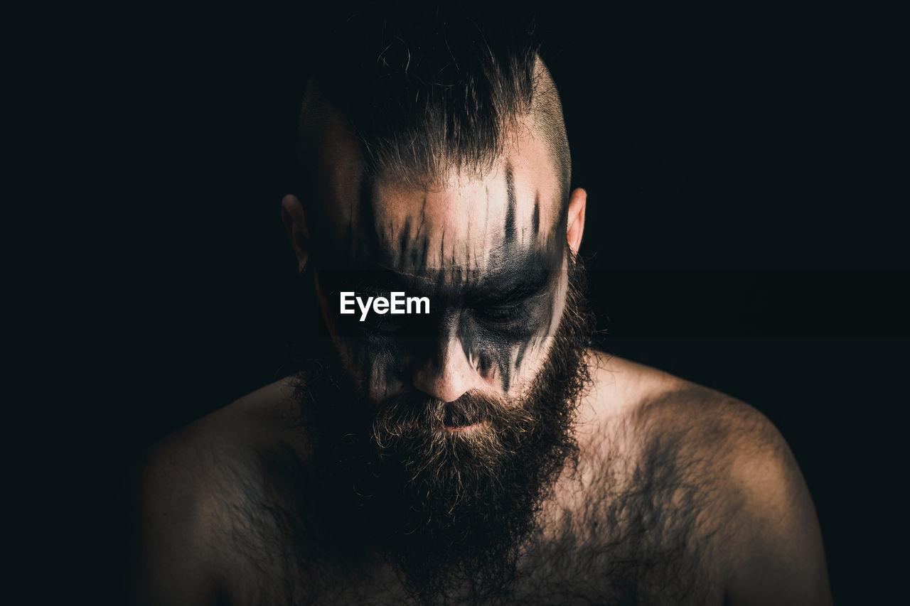 Portrait of shirtless, viking warrior against black background