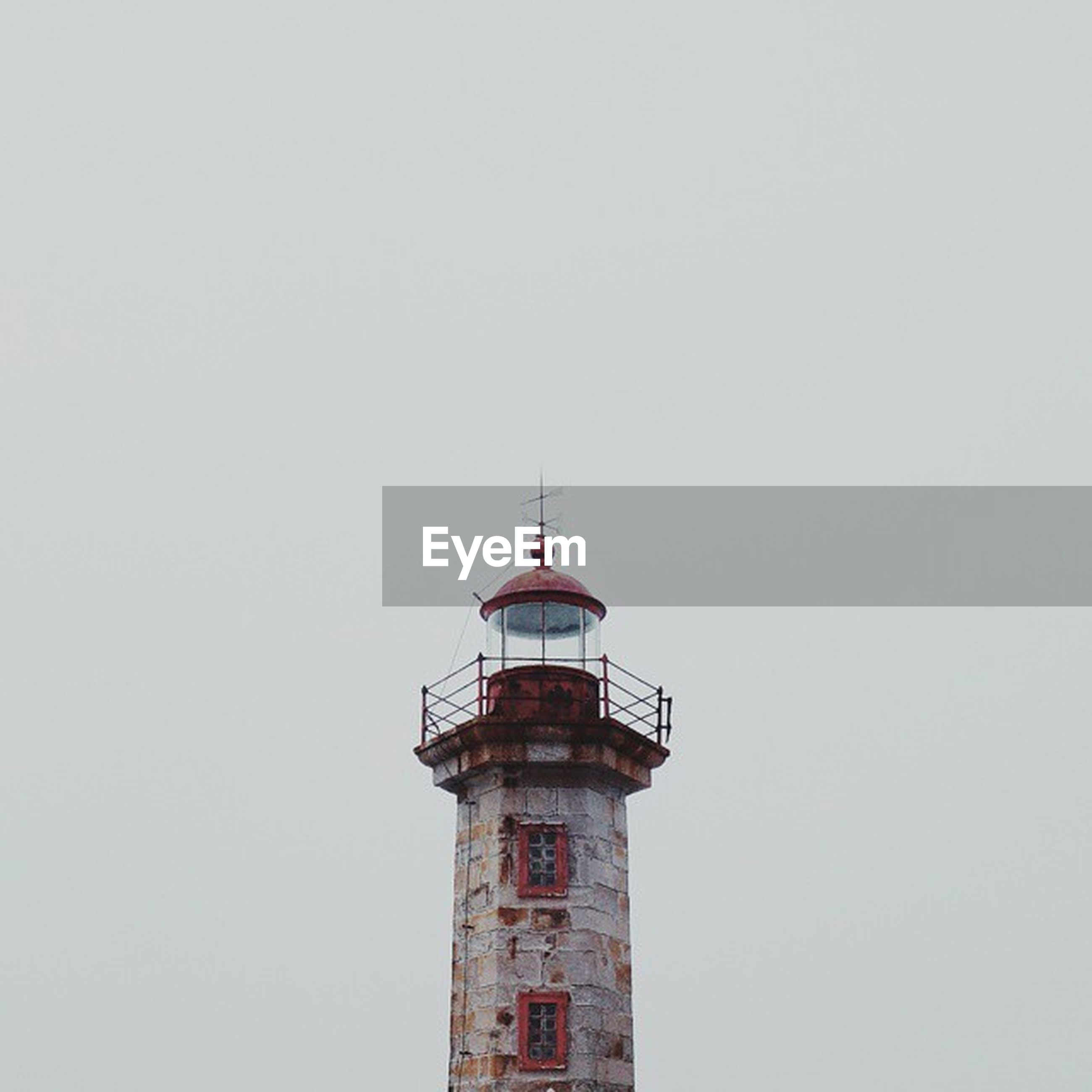 architecture, copy space, built structure, building exterior, clear sky, low angle view, lighthouse, guidance, tower, direction, red, high section, safety, protection, day, outdoors, no people, security, building, tall - high