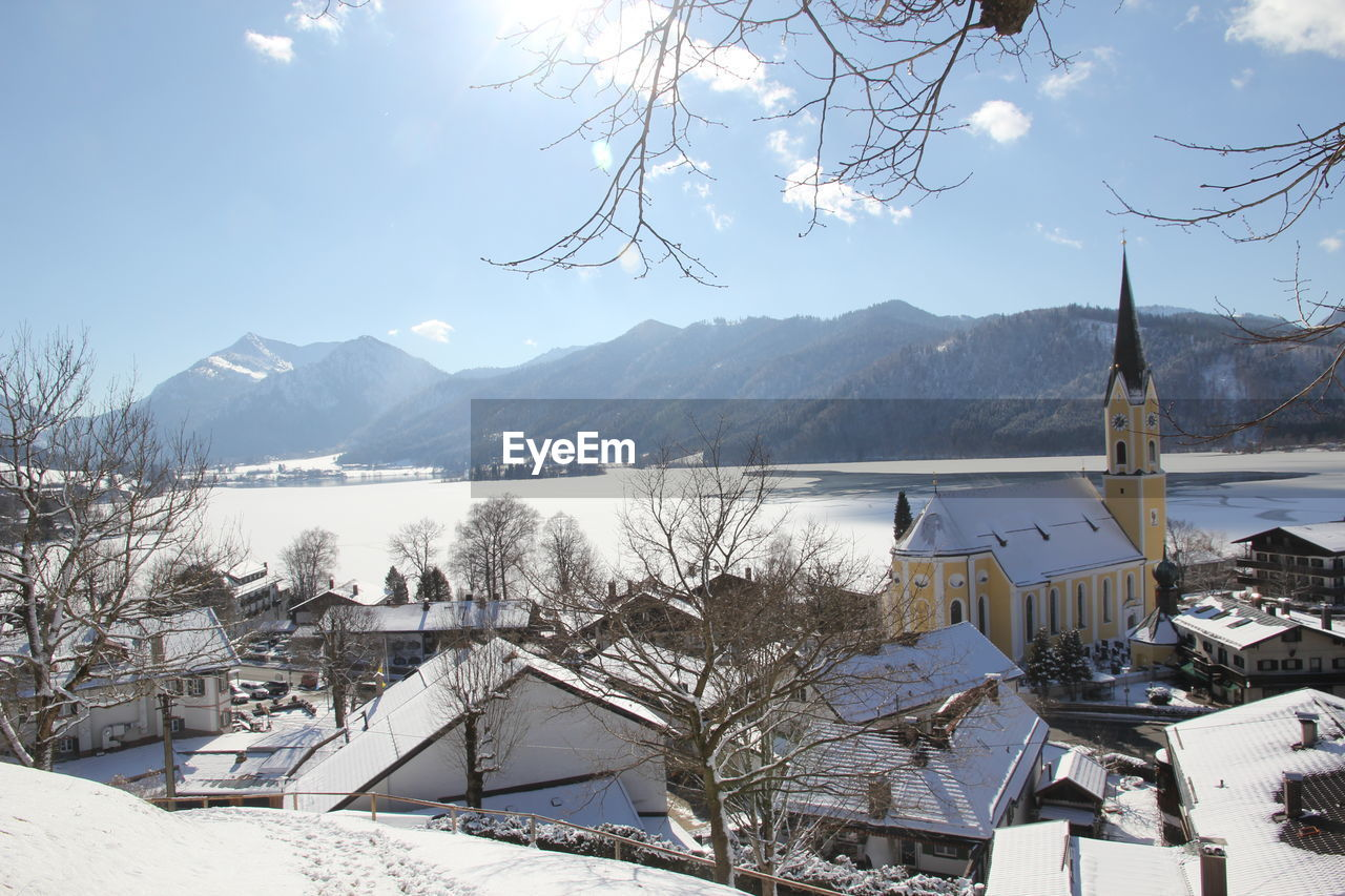 snow, winter, mountain, cold temperature, nature, built structure, building exterior, no people, architecture, outdoors, mountain range, beauty in nature, house, day, sky, high angle view, town, landscape, scenics, extreme weather, roof, water, lake, tree