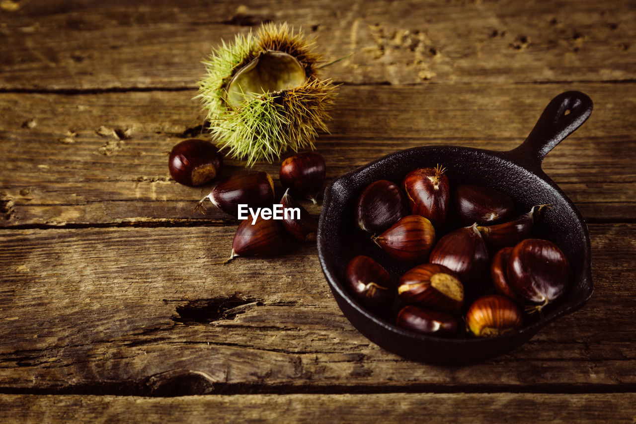 food and drink, food, healthy eating, freshness, wood - material, wellbeing, table, still life, chestnut - food, no people, indoors, fruit, close-up, chestnut, bowl, directly above, nut - food, nut, brown, high angle view