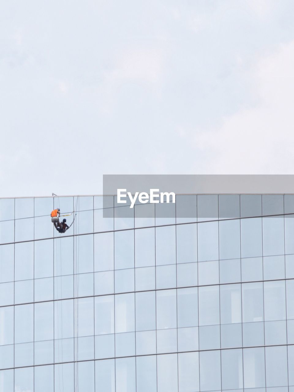 Low Angle View Of Worker Washing Window On Building Against Clear Sky