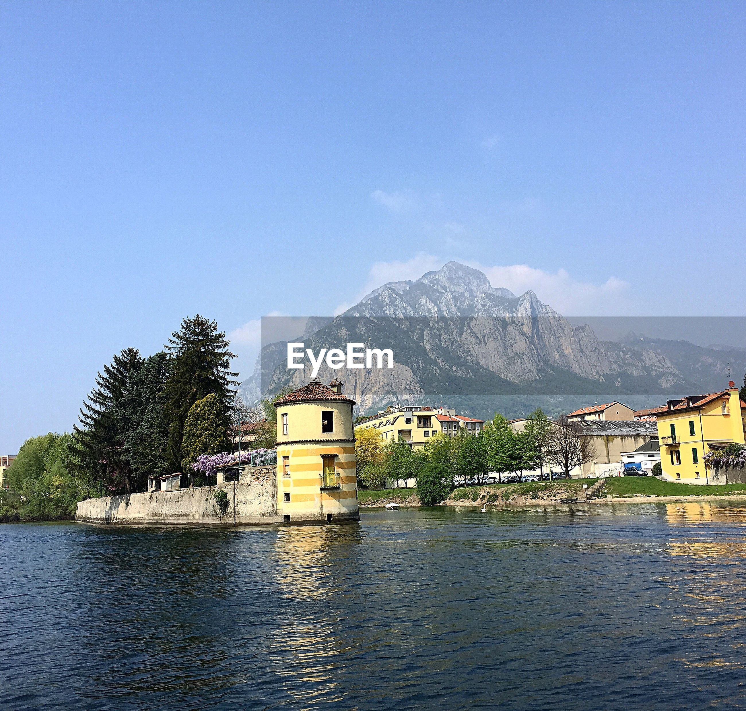sky, water, clear sky, tree, built structure, mountain, building exterior, architecture, outdoors, no people, nature, day, beauty in nature