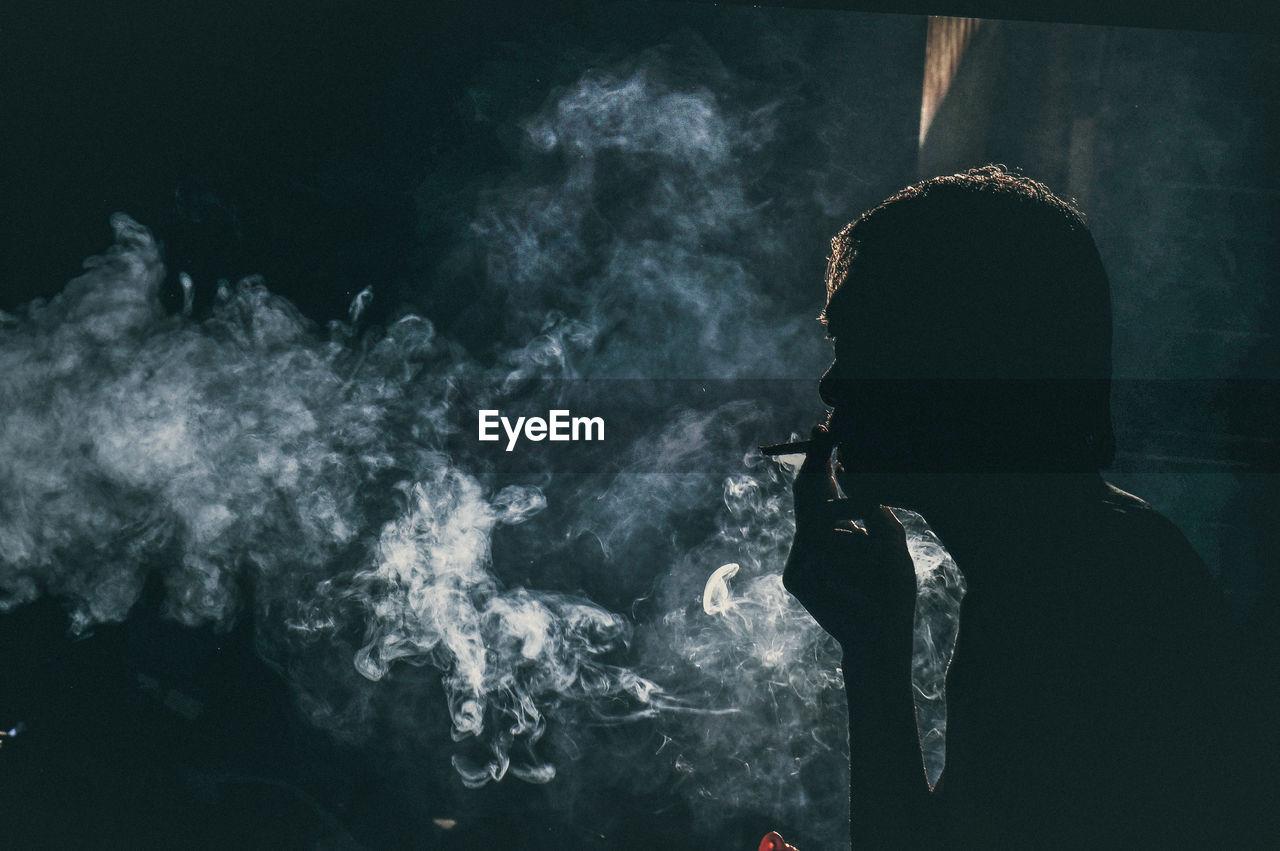 Man Smoking In Darkroom