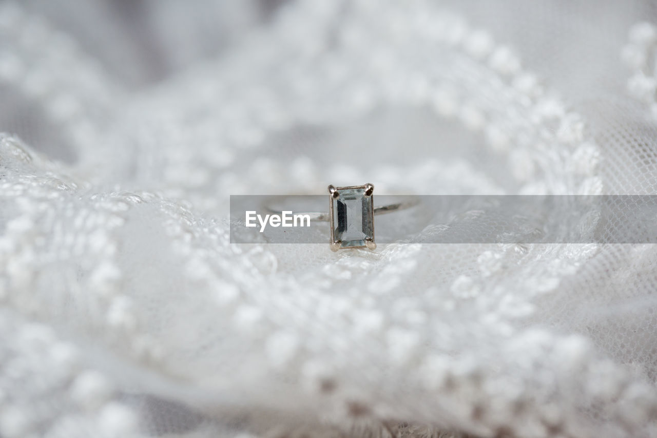 Close-up of wedding ring on white textile
