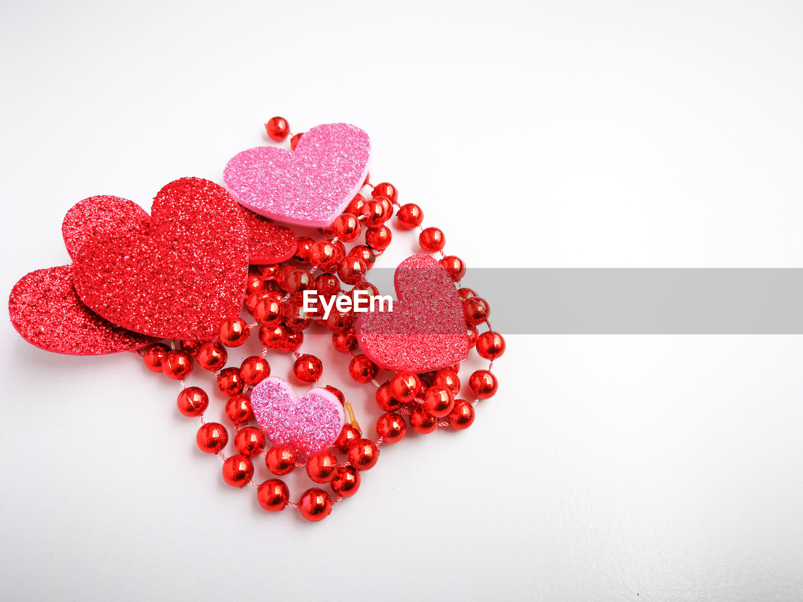 Close-up of heart shapes with red necklace over white background