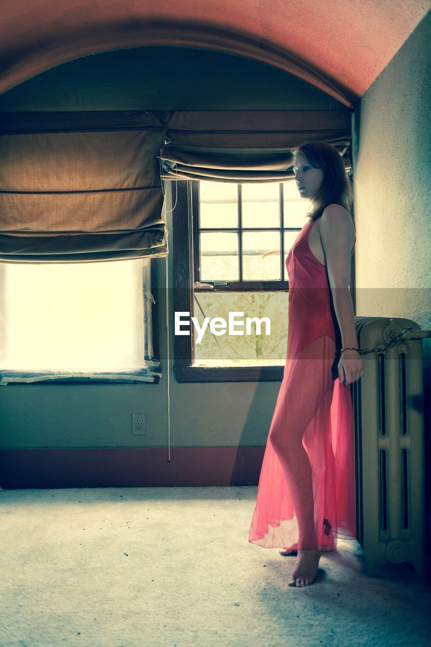 one person, young adult, real people, window, standing, young women, full length, indoors, lifestyles, beautiful woman, day, architecture