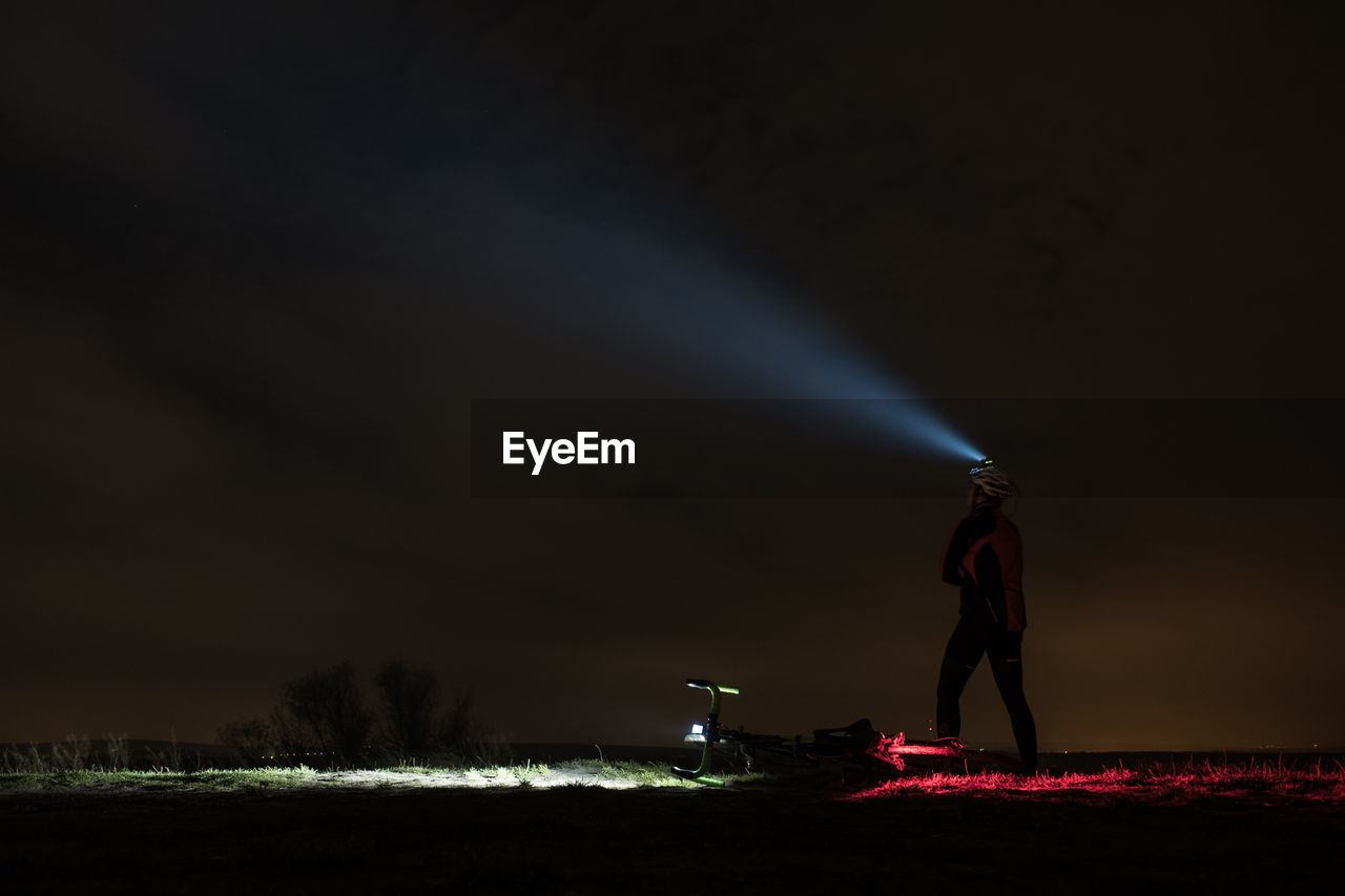 Man With Headlamp Standing On Field Against Sky At Night