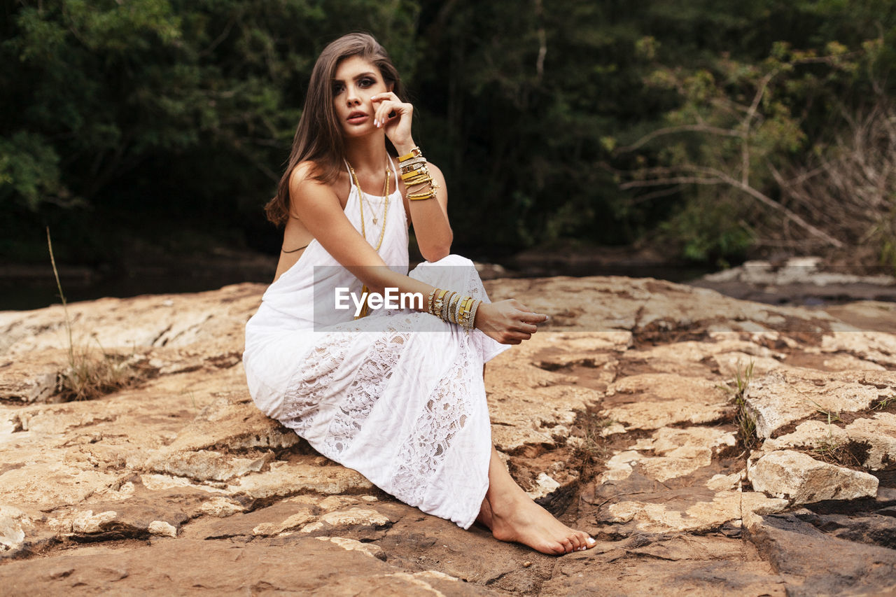 Young Woman Wearing Dress Sitting On Rock Formation At Forest