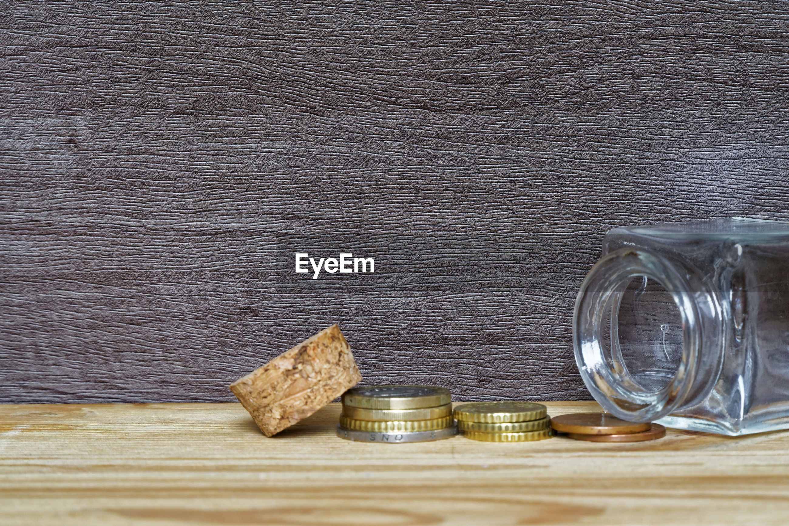 Close-up of coins by glass jar on table