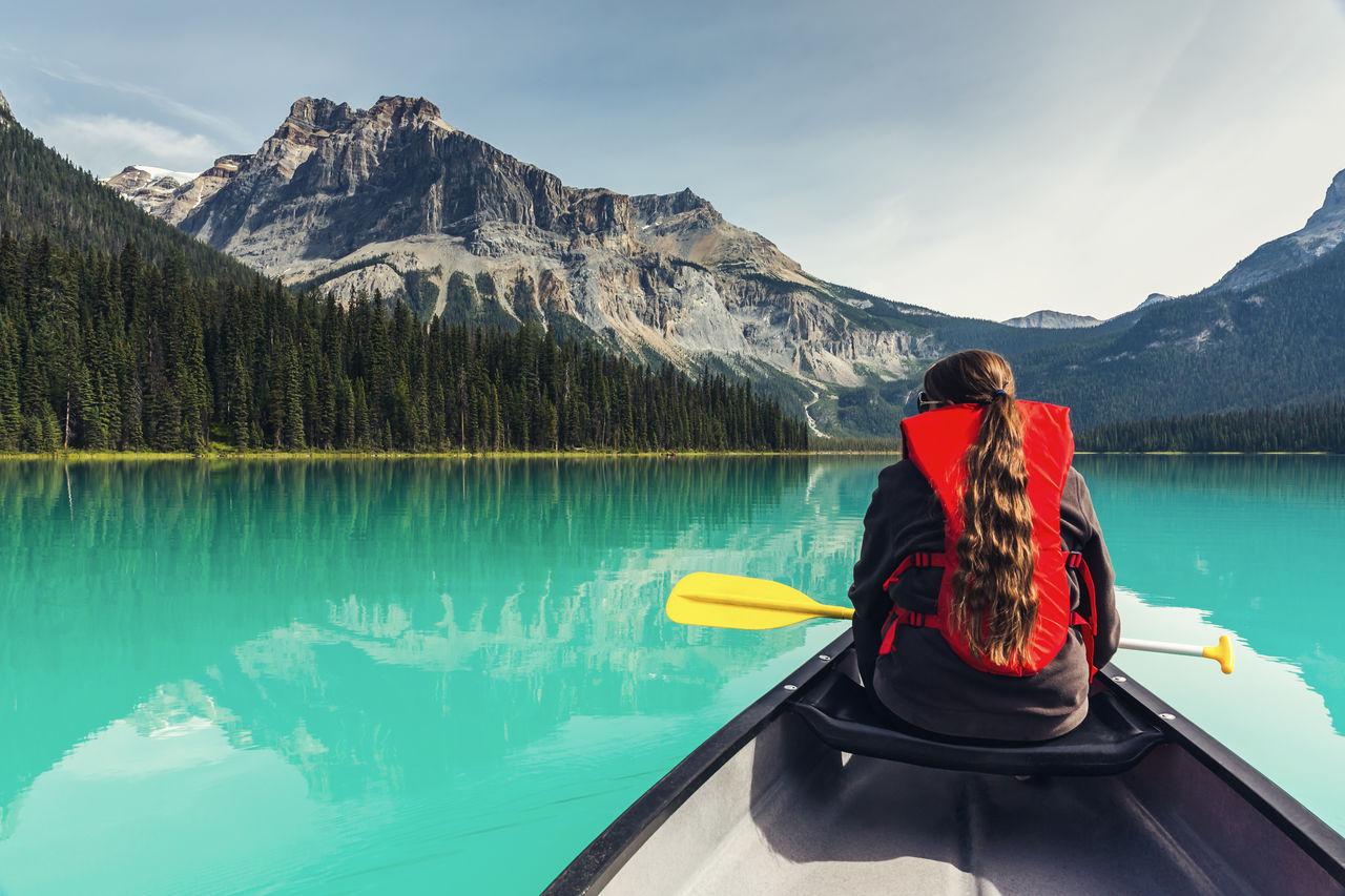 Rear View Of Woman On Kayaking In Lake