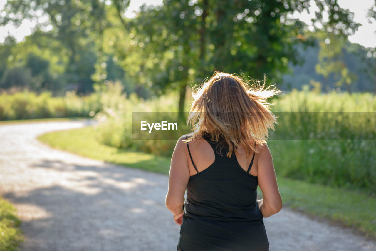 Rear view of young woman walking on road