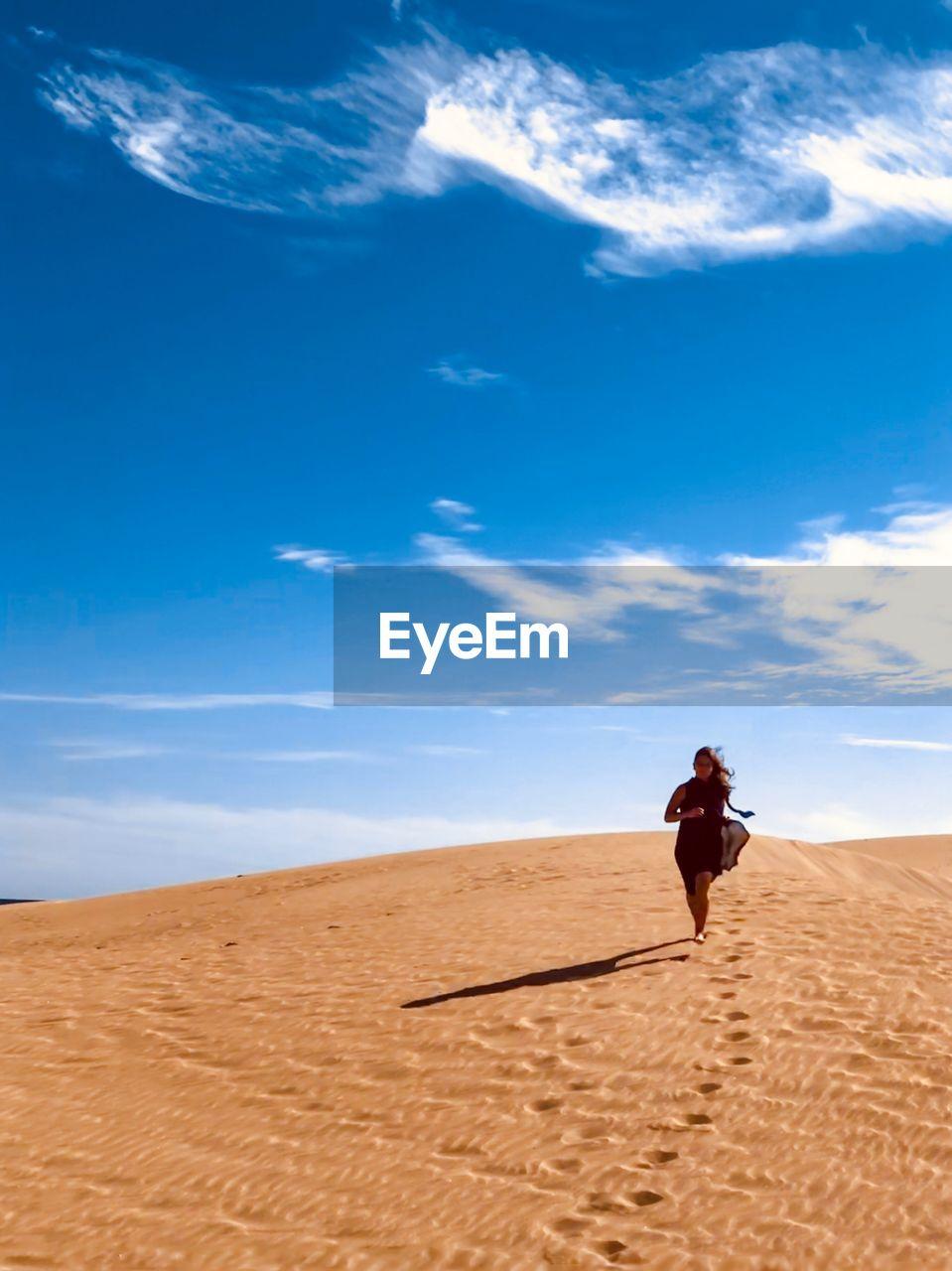 Full length of woman walking on sand in desert against sky