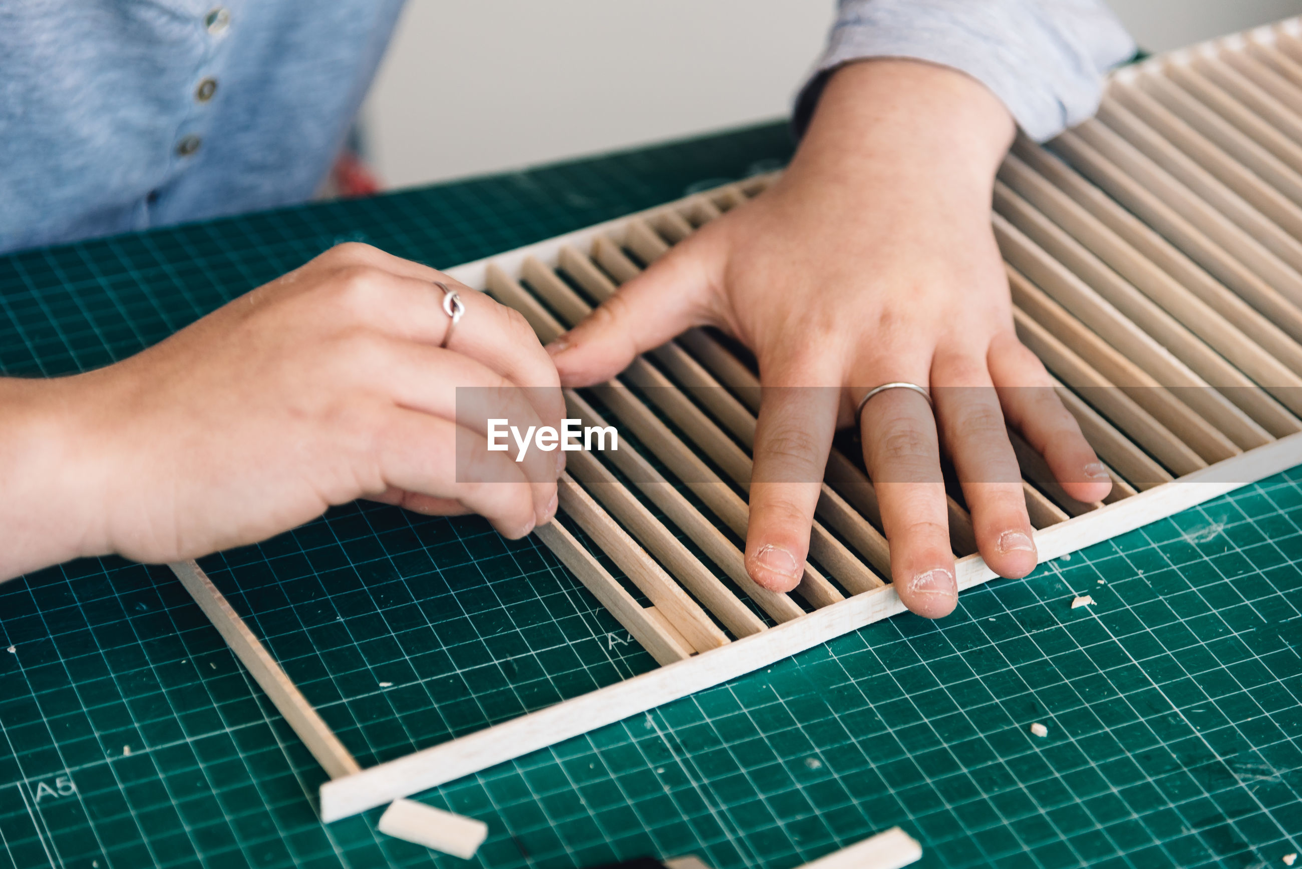 Cropped hands of woman making wooden decor on table