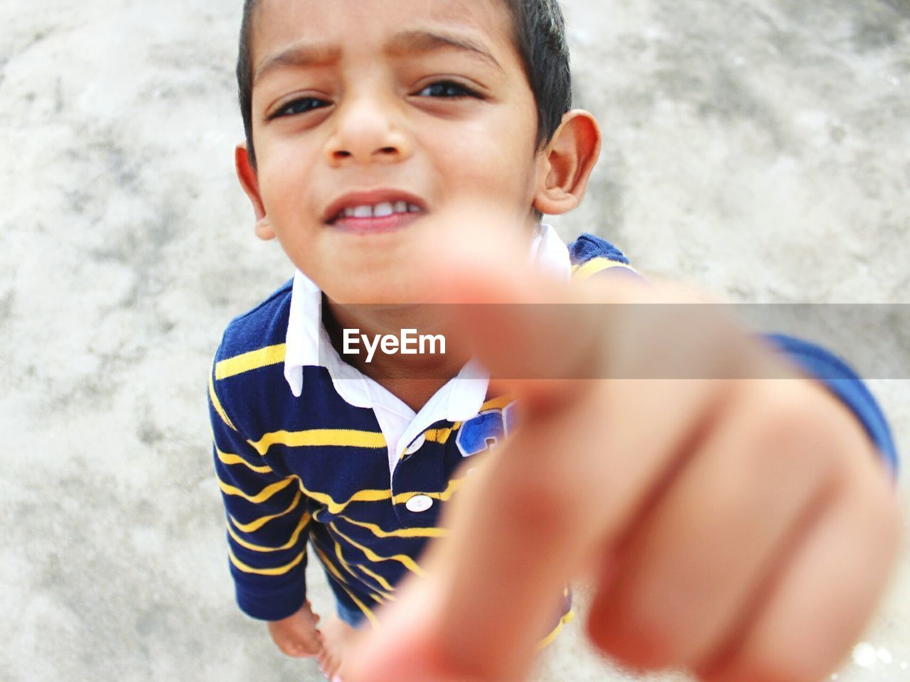 High angle portrait of boy pointing while standing on footpath