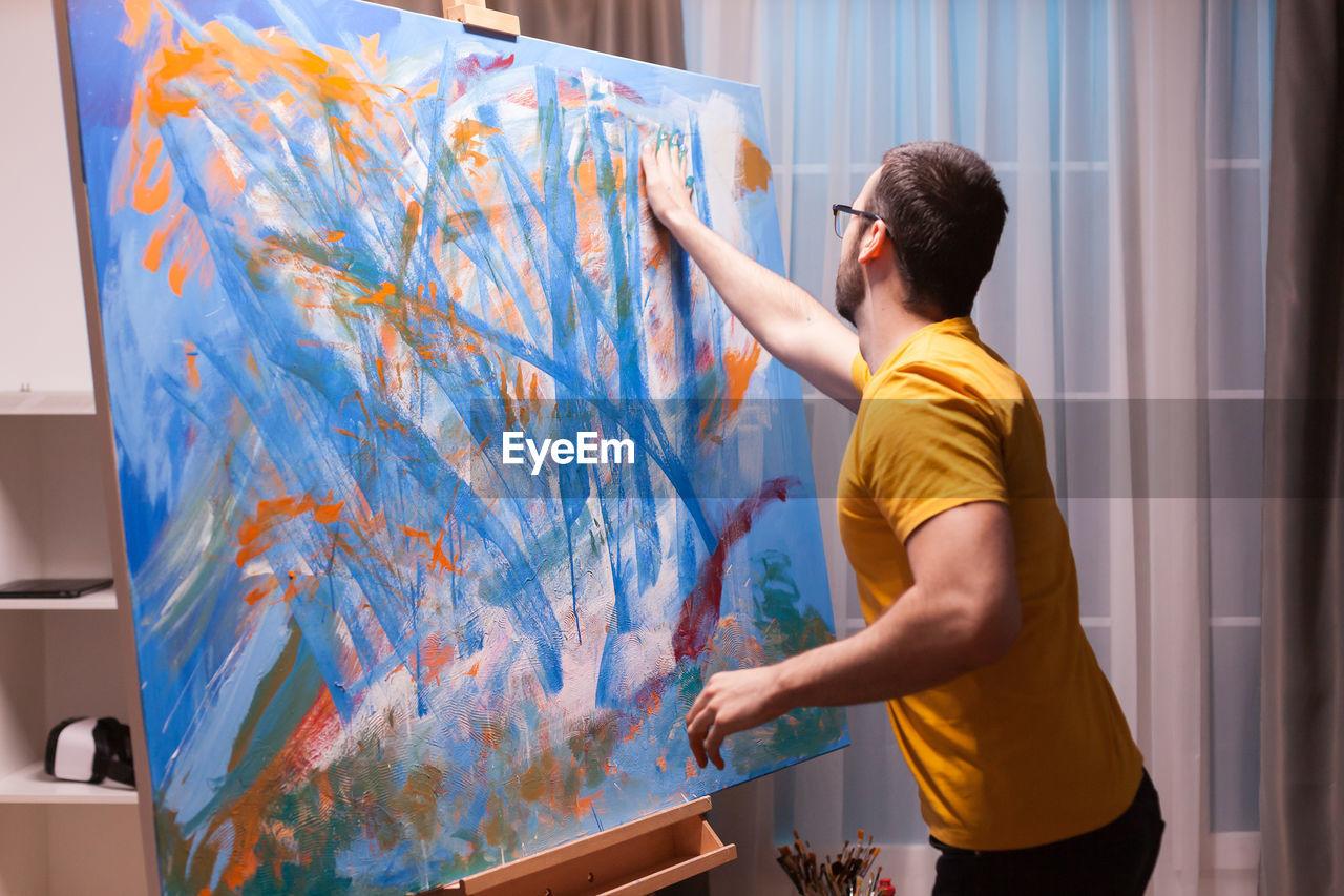 REAR VIEW OF MAN LOOKING AT GRAFFITI WALL