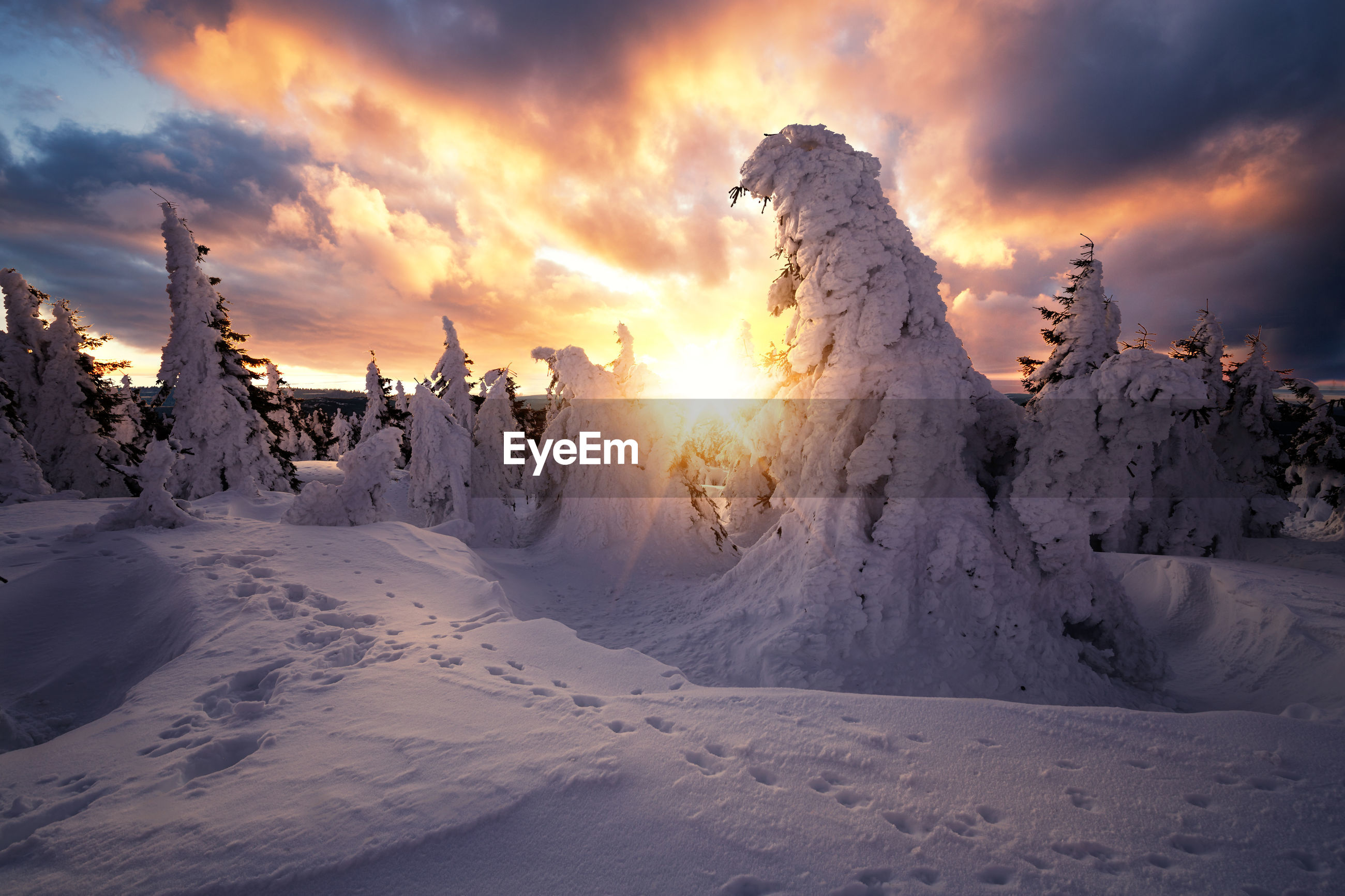 Panoramic view of snow covered land against sky during sunset