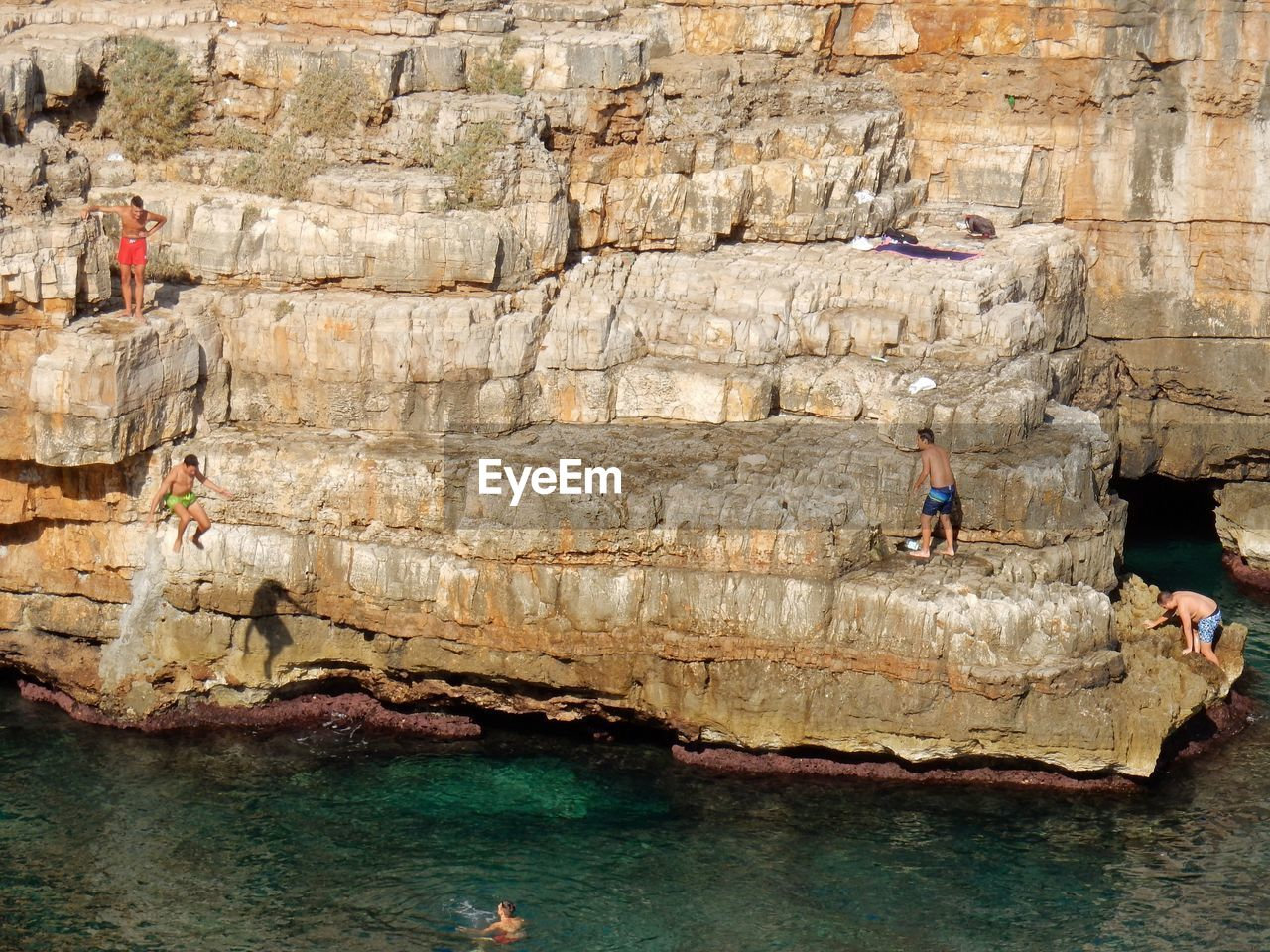 water, solid, sea, rock formation, rock - object, rock, group of people, nature, day, adventure, real people, land, people, outdoors, architecture, leisure activity, men, travel, beach