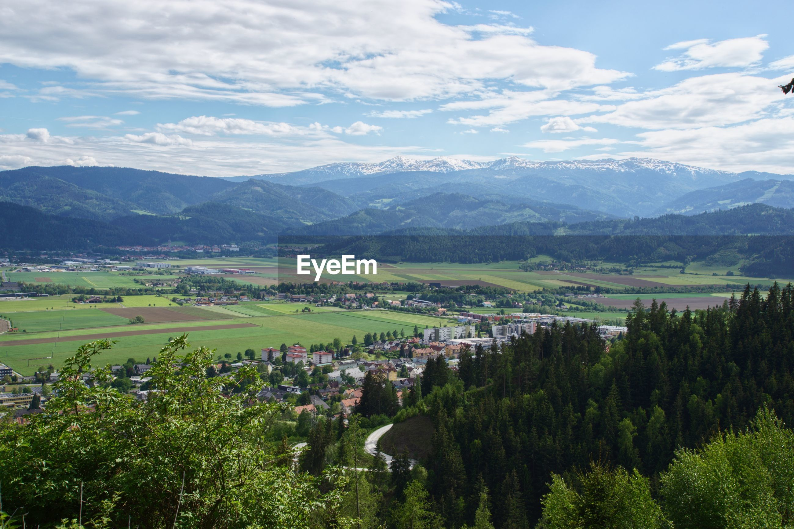 Scenic view of townscape by mountains against sky