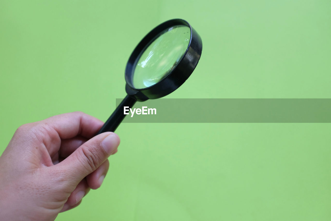 human hand, hand, human body part, human finger, magnifying glass, finger, holding, one person, indoors, unrecognizable person, body part, real people, studio shot, green color, copy space, colored background, lifestyles, leisure activity, green background