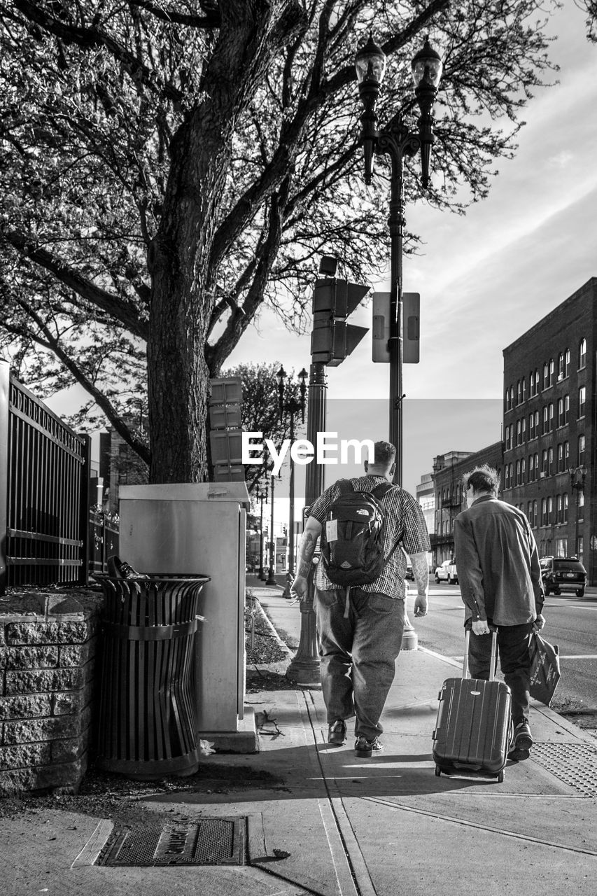 real people, full length, men, rear view, tree, building exterior, built structure, city, plant, architecture, day, nature, people, lifestyles, leisure activity, street, footpath, casual clothing, outdoors, walking, uniform