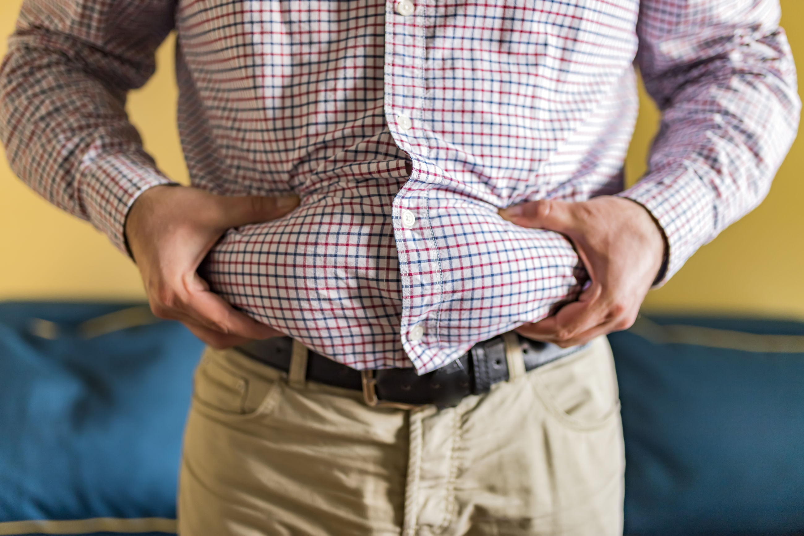 Midsection of man holding belly fat at home