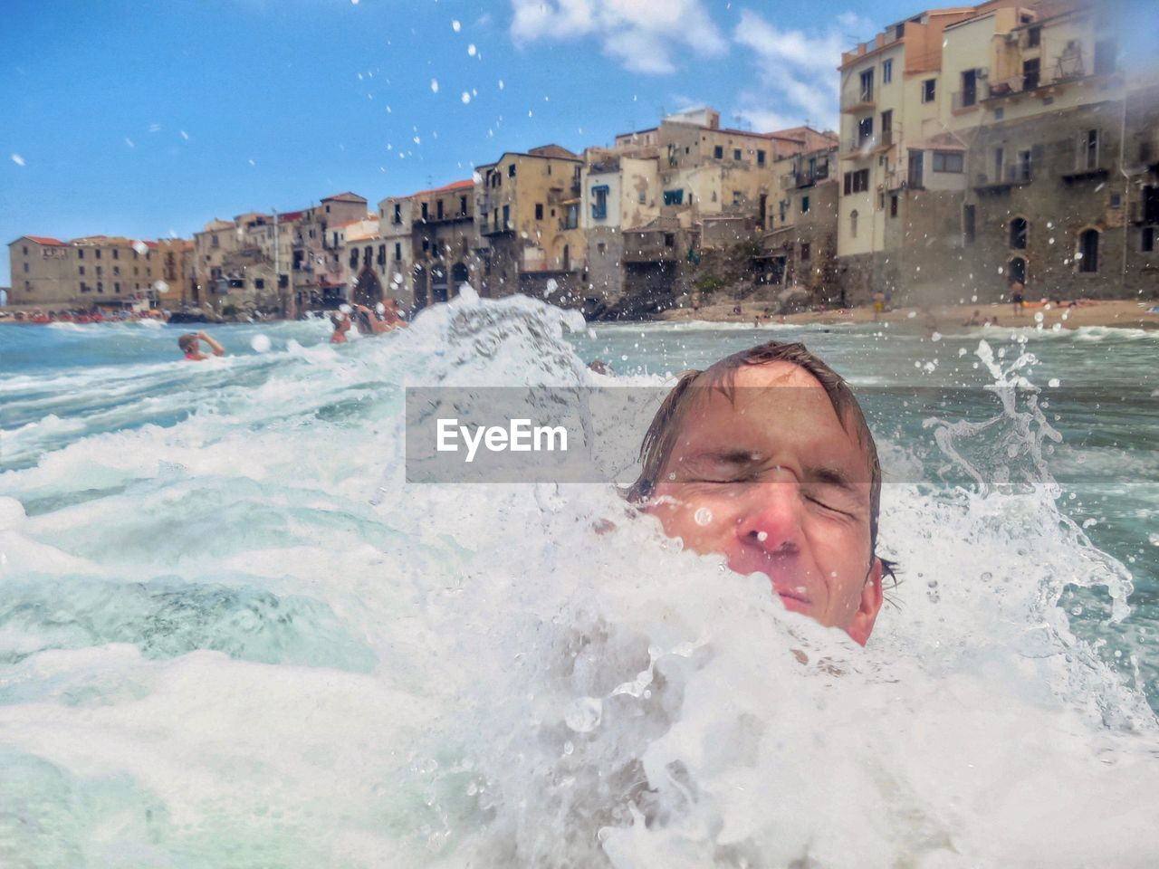 Close-up of man swimming in sea against buildings