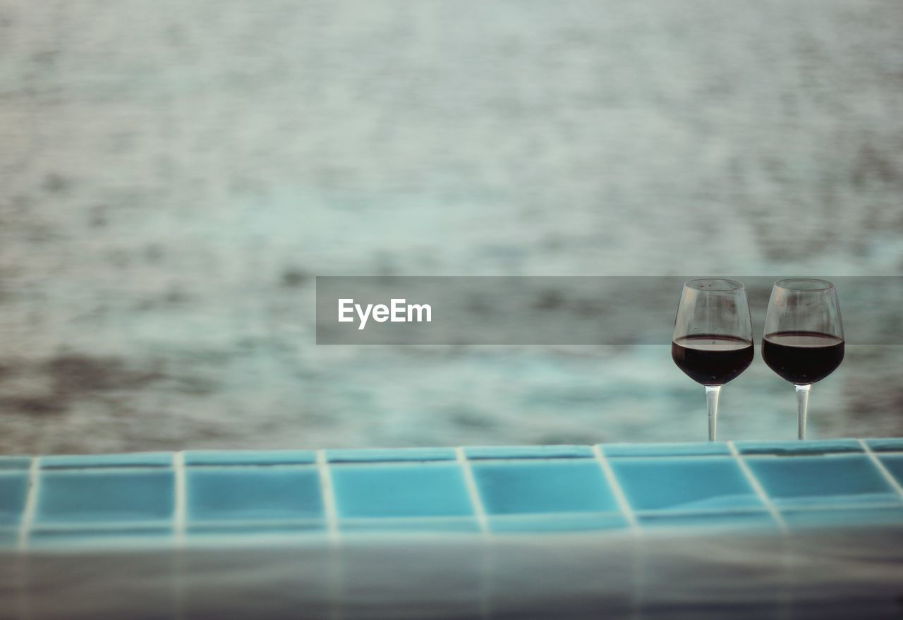 Close-Up Of Wineglasses By Swimming Pool