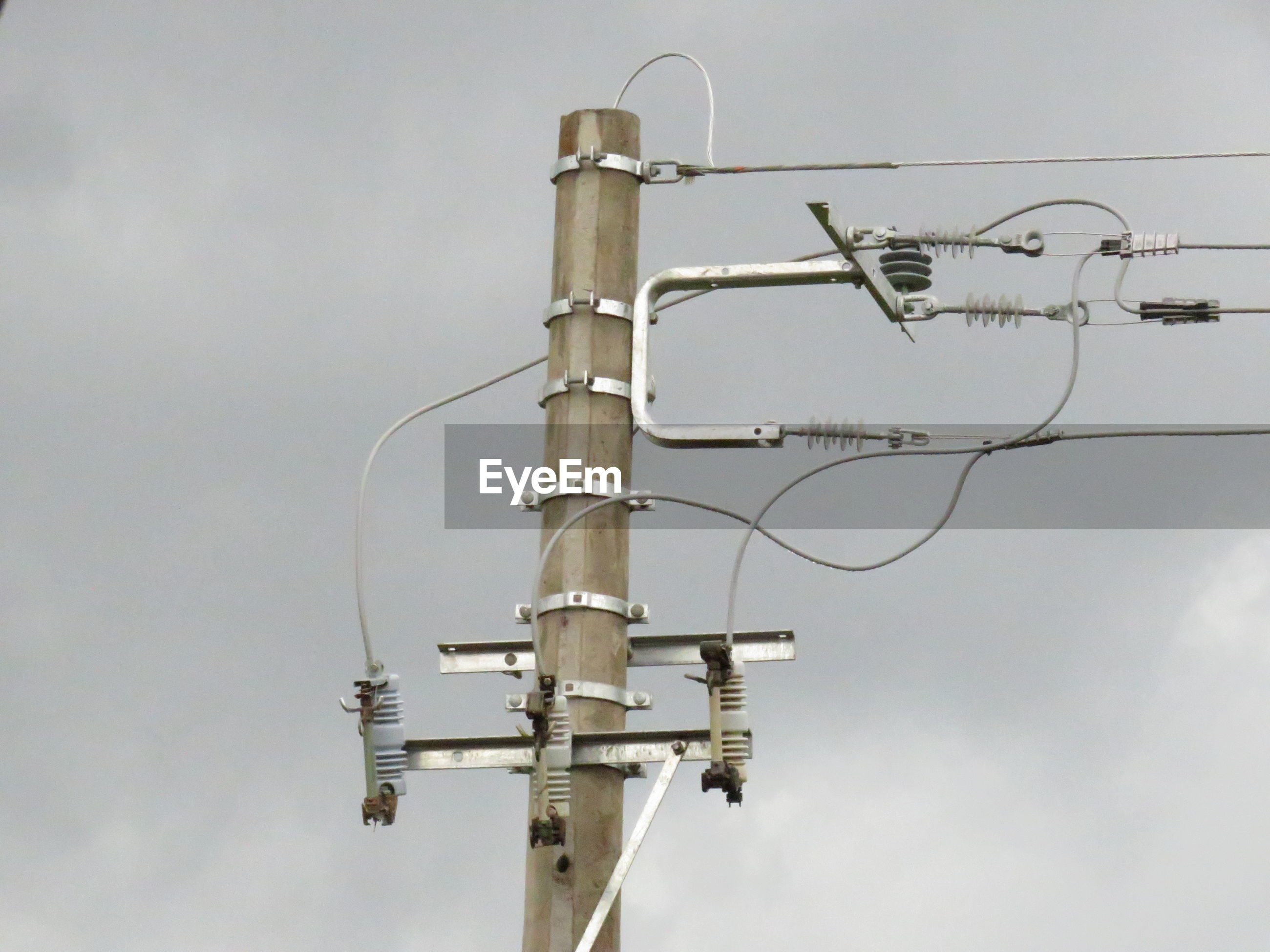 LOW ANGLE VIEW OF CRANE ON POWER LINES AGAINST SKY