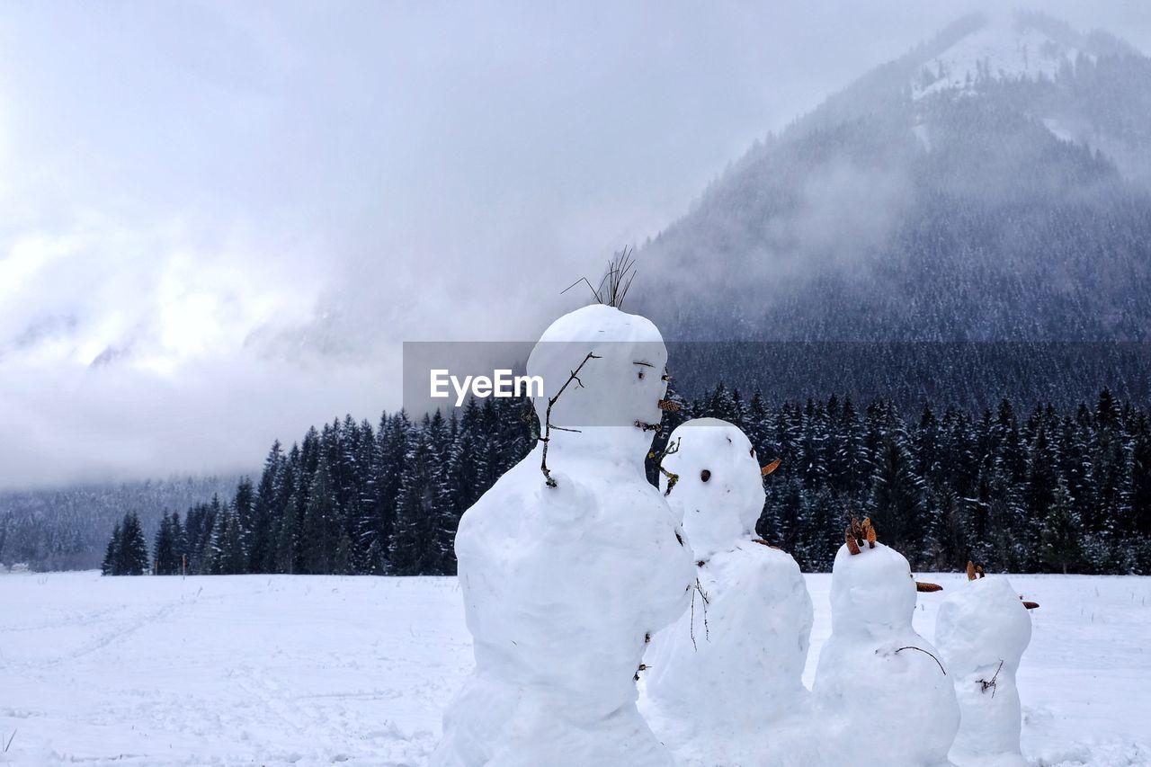 Snowman On Field Against Cloudy Sky