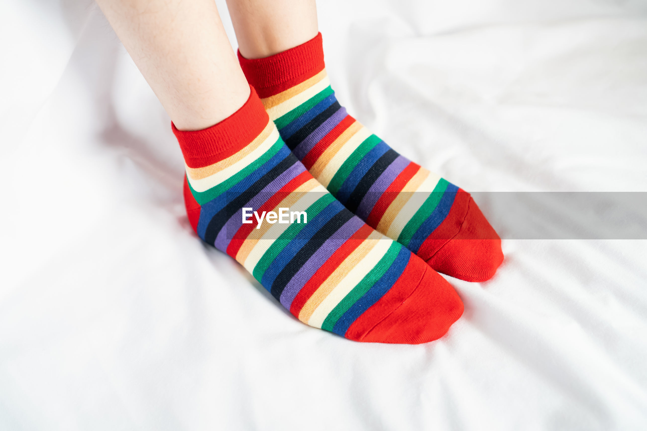 Low section of woman wearing colorful socks on bed