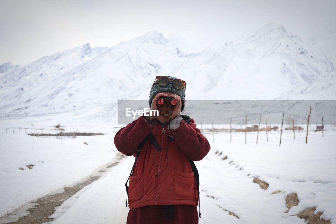 Boy Looking Through Binoculars Against Snowcapped Mountains