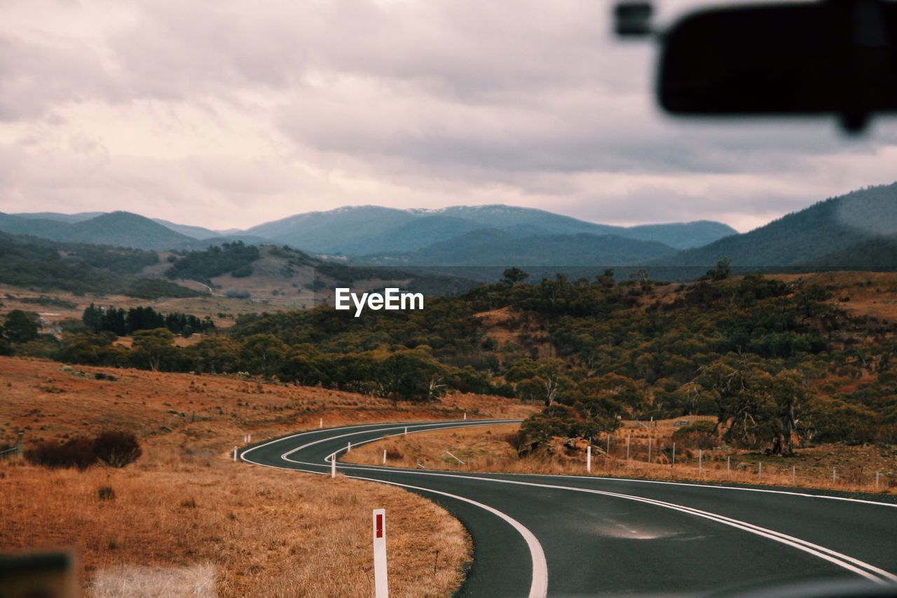 Empty Road Leading Towards Mountains Seen Through Car Windshield
