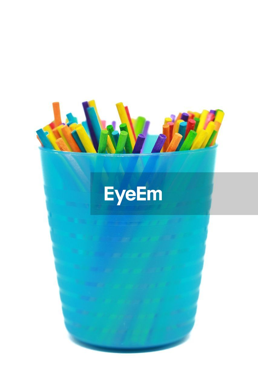 Close-Up Of Colored Pencils In Blue Case Over White Background