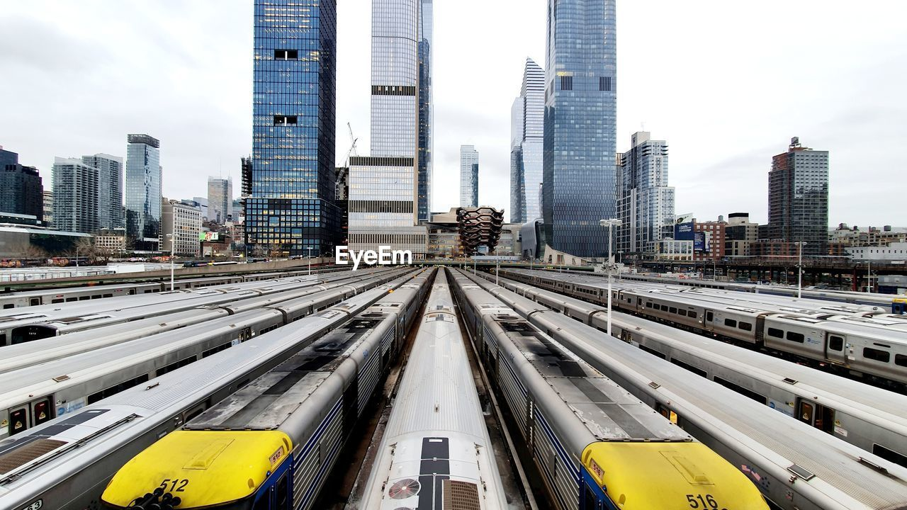 Trains lined up in west side yard, nyc in january 2020 with cityscape in background.