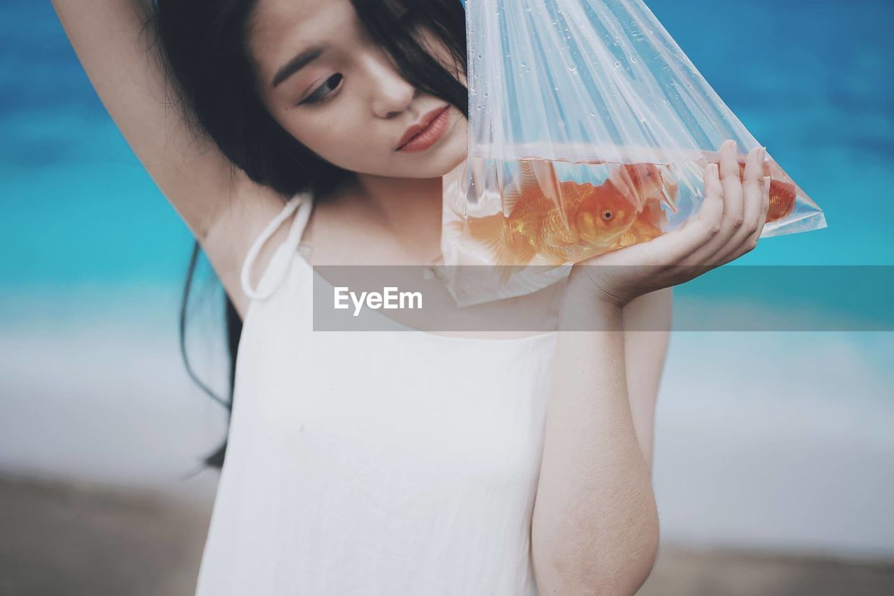 Close-Up Of Young Woman Holding Fish In Plastic Bag At Beach