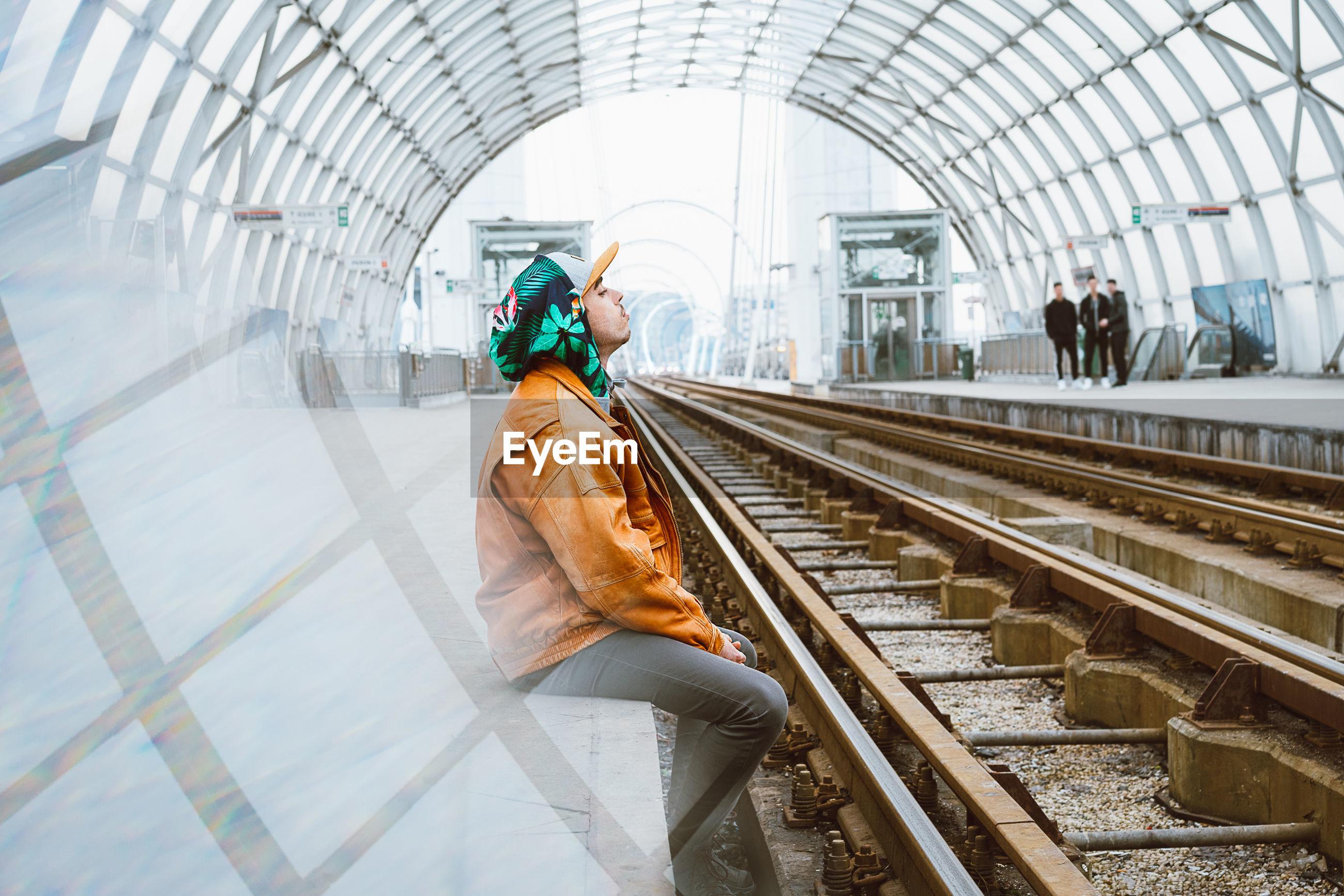 Side view of man sitting at railroad station platform