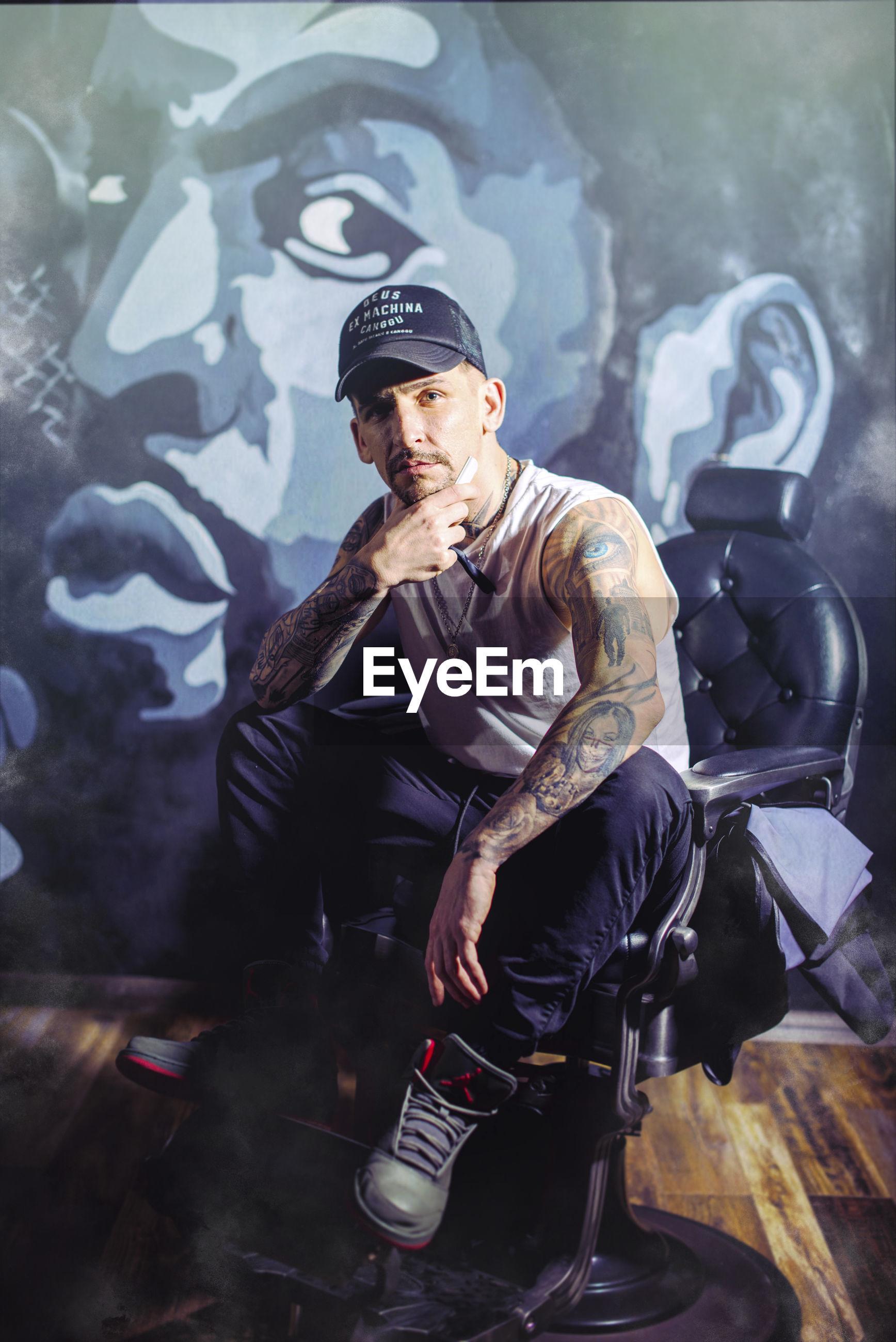 Portrait of man sitting on chair against graffiti wall