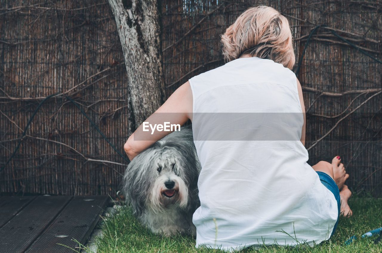 mammal, domestic animals, one animal, pets, domestic, real people, canine, dog, one person, tree, vertebrate, plant, lifestyles, leisure activity, women, day, casual clothing, hair, pet owner, hairstyle, outdoors