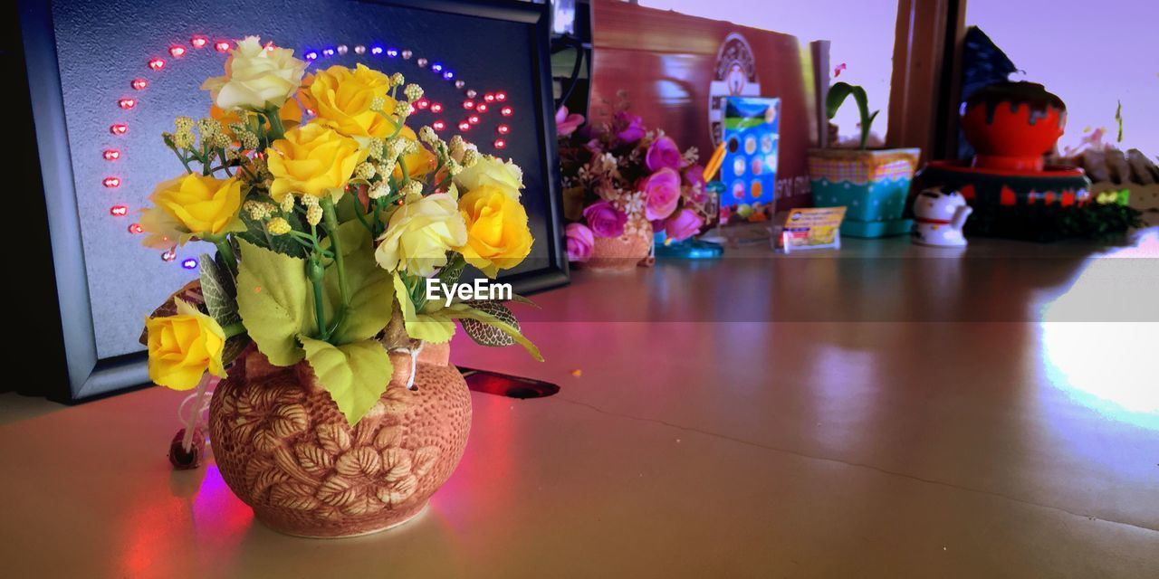 flower, indoors, vase, table, home interior, yellow, petal, freshness, no people, fragility, multi colored, flower head, close-up, beauty in nature, day