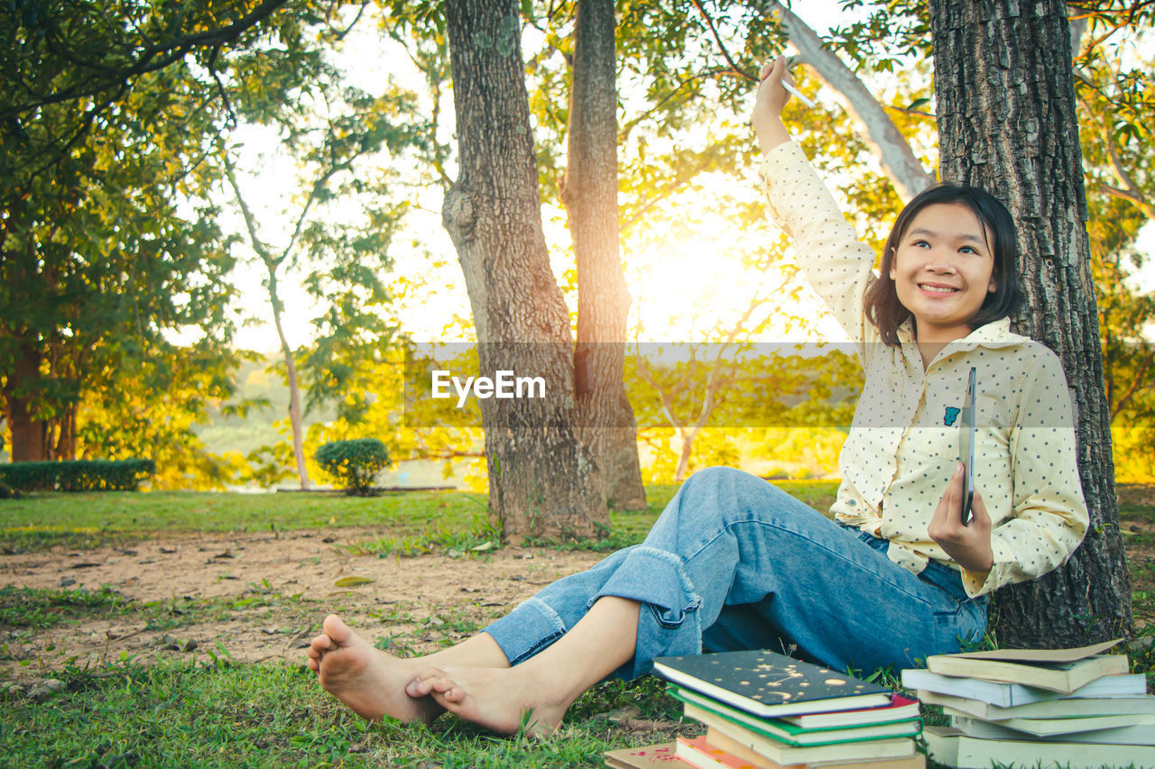 PORTRAIT OF SMILING YOUNG WOMAN SITTING ON BOOK AGAINST TREE