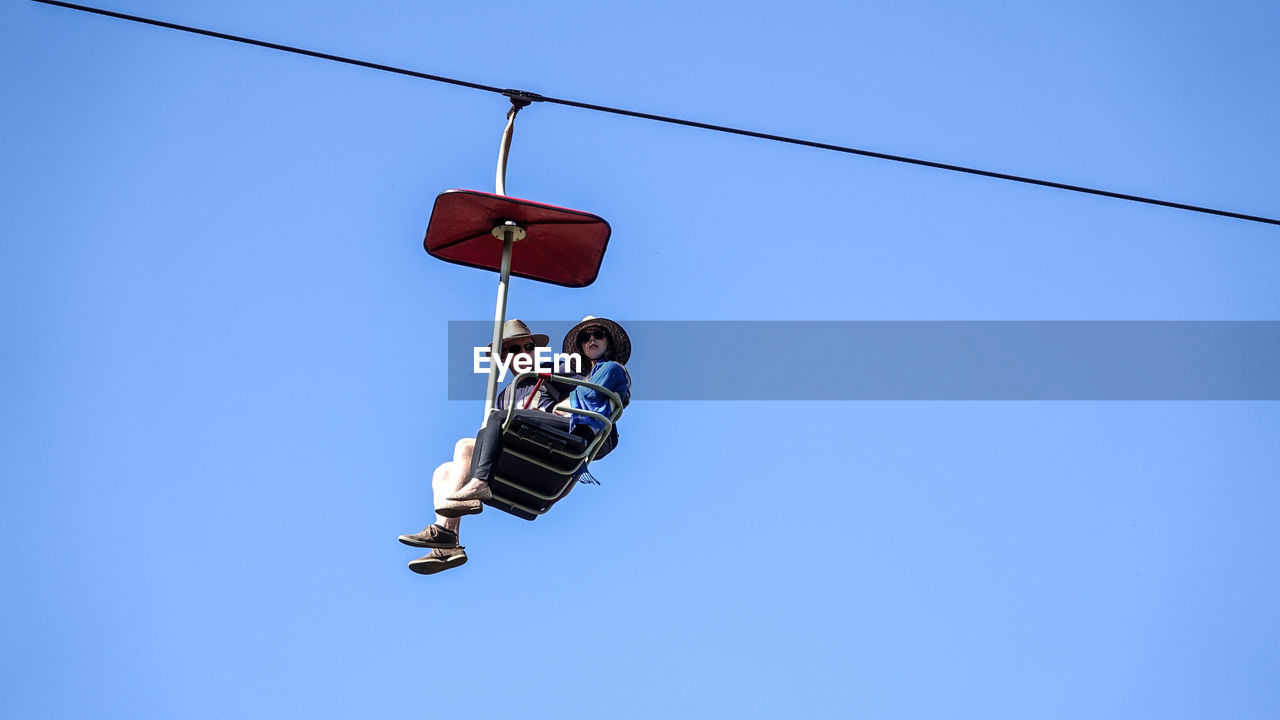 LOW ANGLE VIEW OF MEN HANGING AGAINST CLEAR BLUE SKY