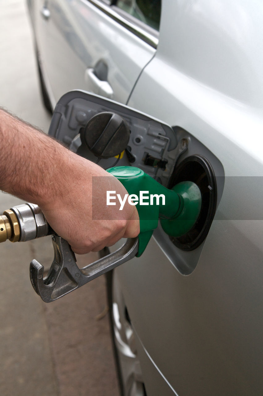 Close-Up Of Man Filling Fuel In Car
