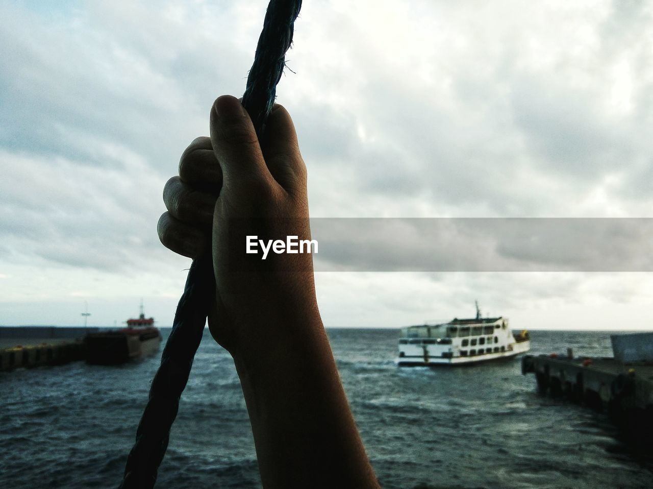 Cropped Hand Holding Rope While Traveling In Boat Against Cloudy Sky