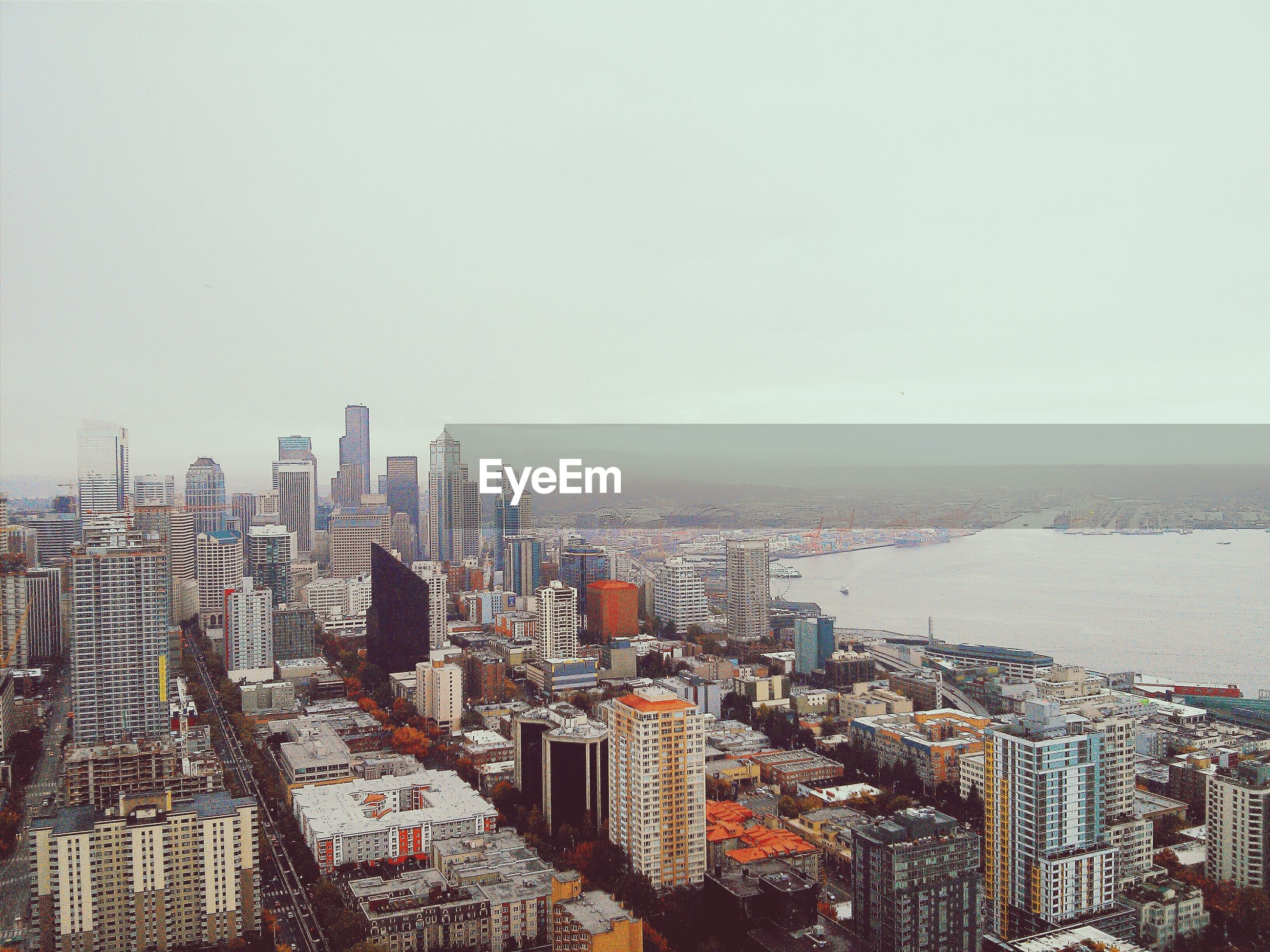 High angle view of cityscape and lake against sky