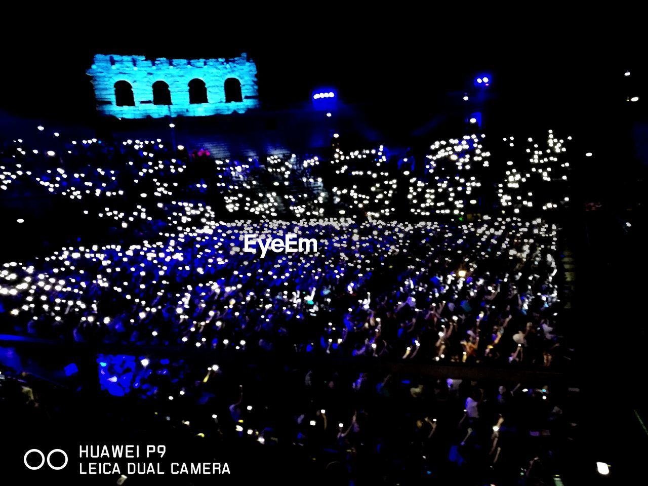illuminated, night, large group of people, crowd, arts culture and entertainment, music, audience, real people, performance, stage light, stage - performance space, event, celebration, blue, nightlife, popular music concert, indoors, togetherness, men, fan - enthusiast, people