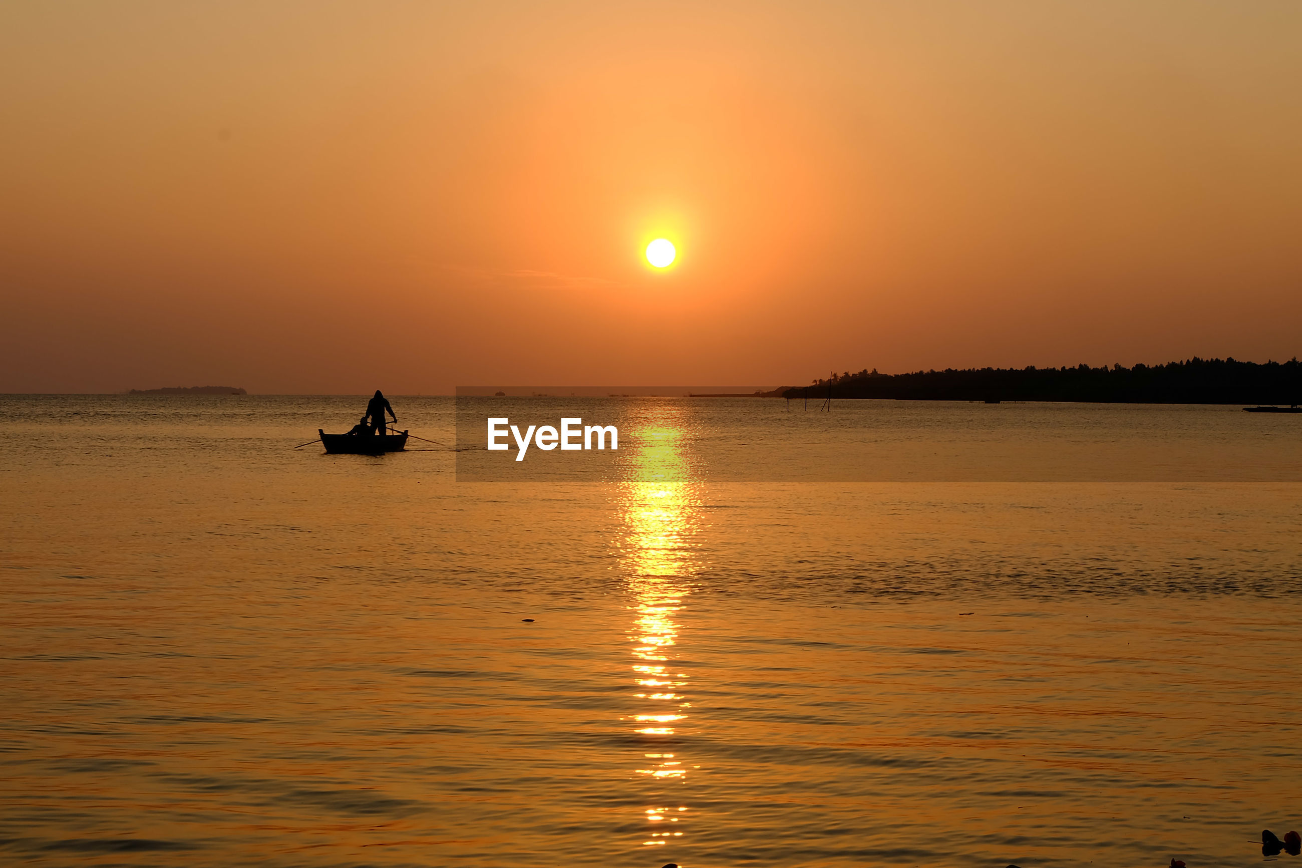 Scenic view of two people on boat with sunset over sea